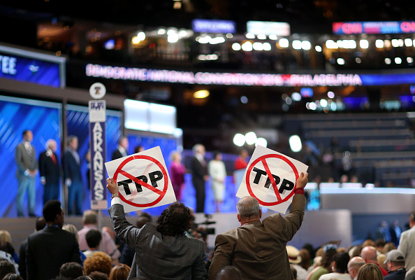 Delegates hold signs against the Trans-Pacific Partnership (TPP) during the Democratic National Convention (DNC) in Philadelphia, Pennsylvania, U.S., on Monday, July 25, 2016.