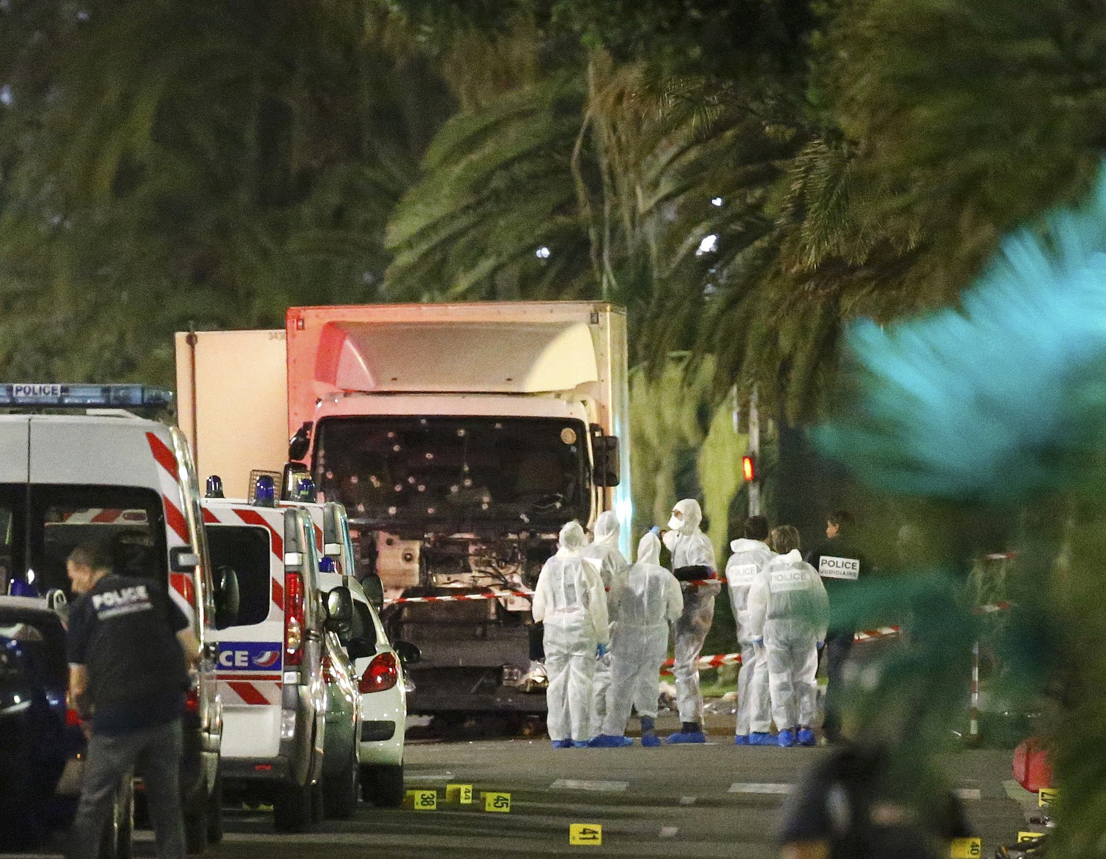 French police forces and forensic officers stand next to a truck in Nice, France, on July 15, 2016, after authorities said it ran into a crowd celebrating Bastille Day on the Promenade des Anglais, killing at least 84 people.