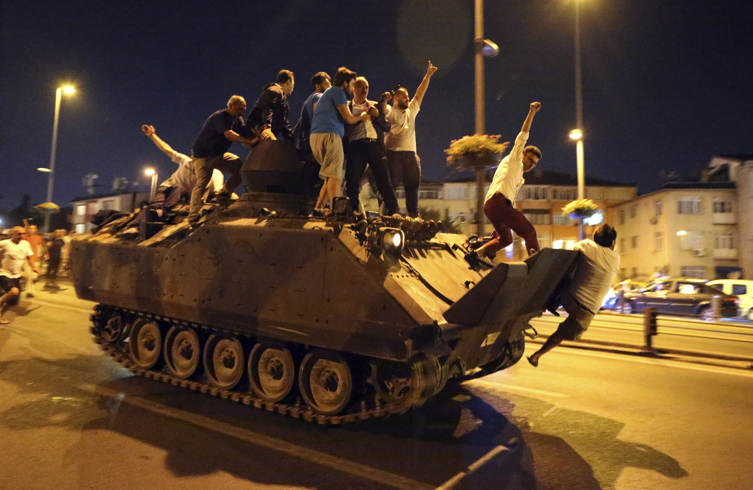 People occupy a tank in Istanbul, Turkey, on July 16, 2016. Turkish Prime Minister Yildirim reportedly said that the Turkish military was involved in an attempted coup d'etat. The Turkish military meanwhile stated it had taken over control.