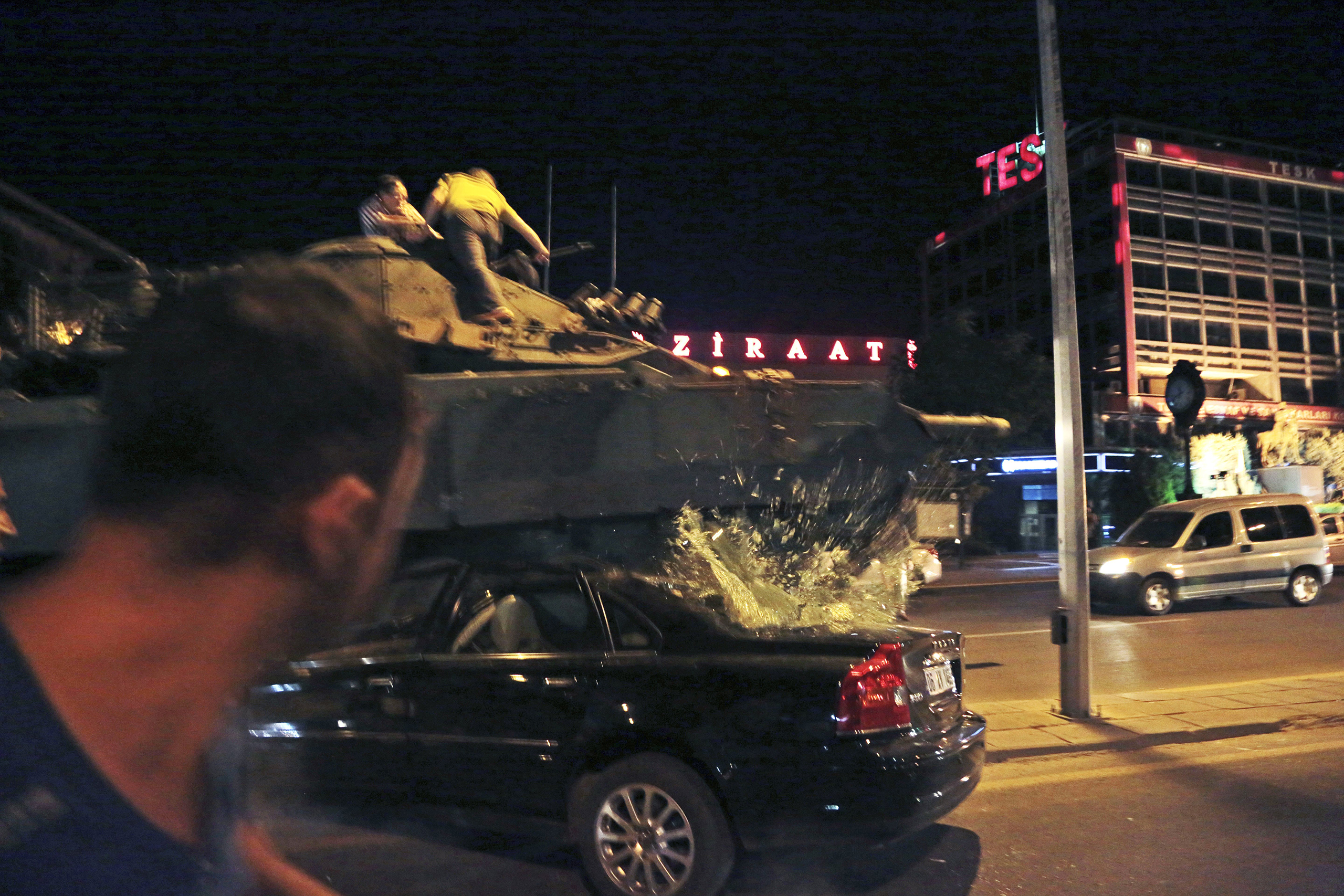 A tank moving into position crashes over a car as people attempt to stop it in Ankara, Turkey, on July 15, 2016.