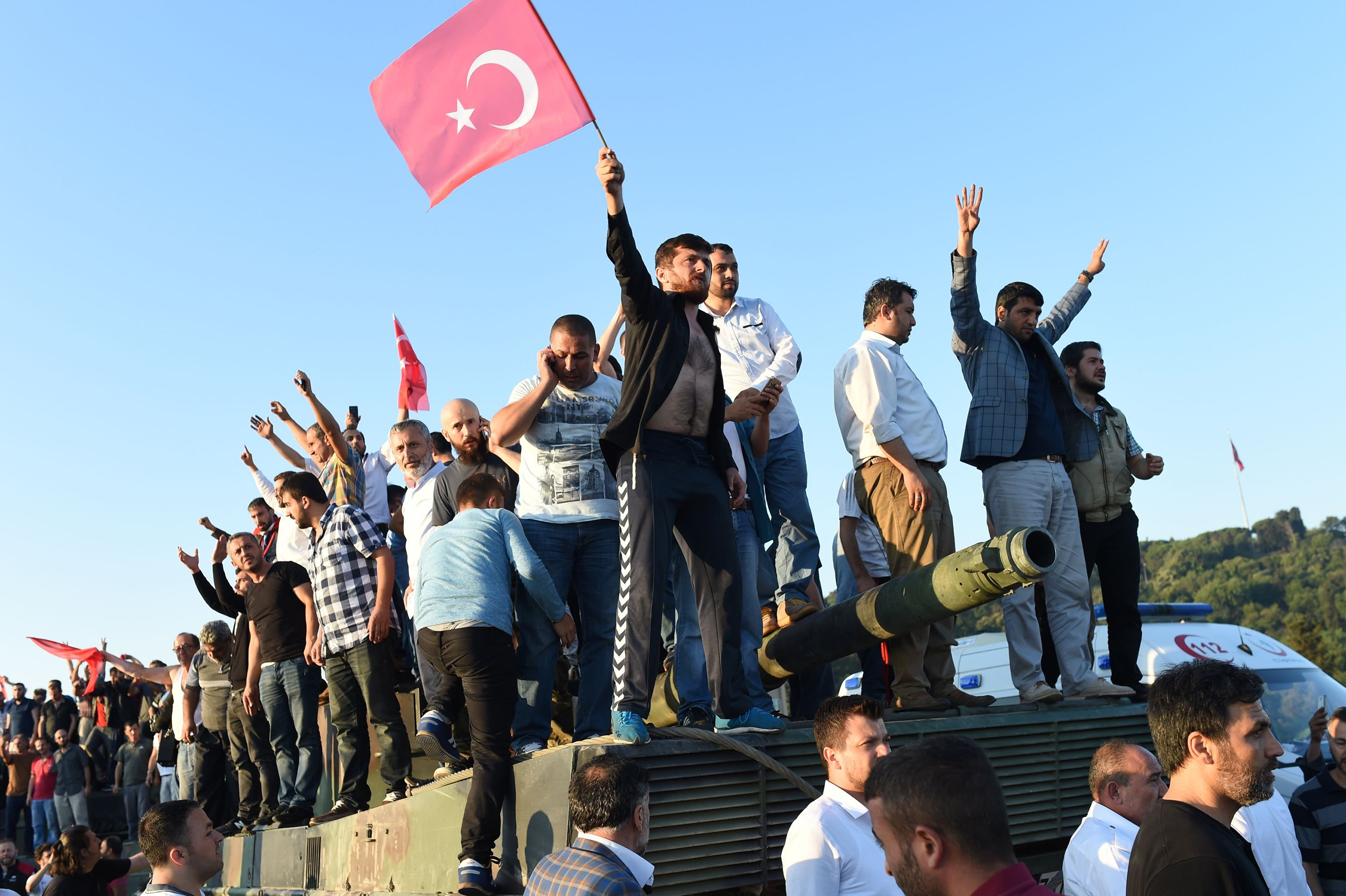 A group of men stand atop a tank the morning after a military coup attempt against the government of Recep Tayyip Erdogan turned violent, killing dozens and leaving hundreds of others detained, on the Bosphorus Bridge in Istanbul, Turkey, on July 16, 2016.