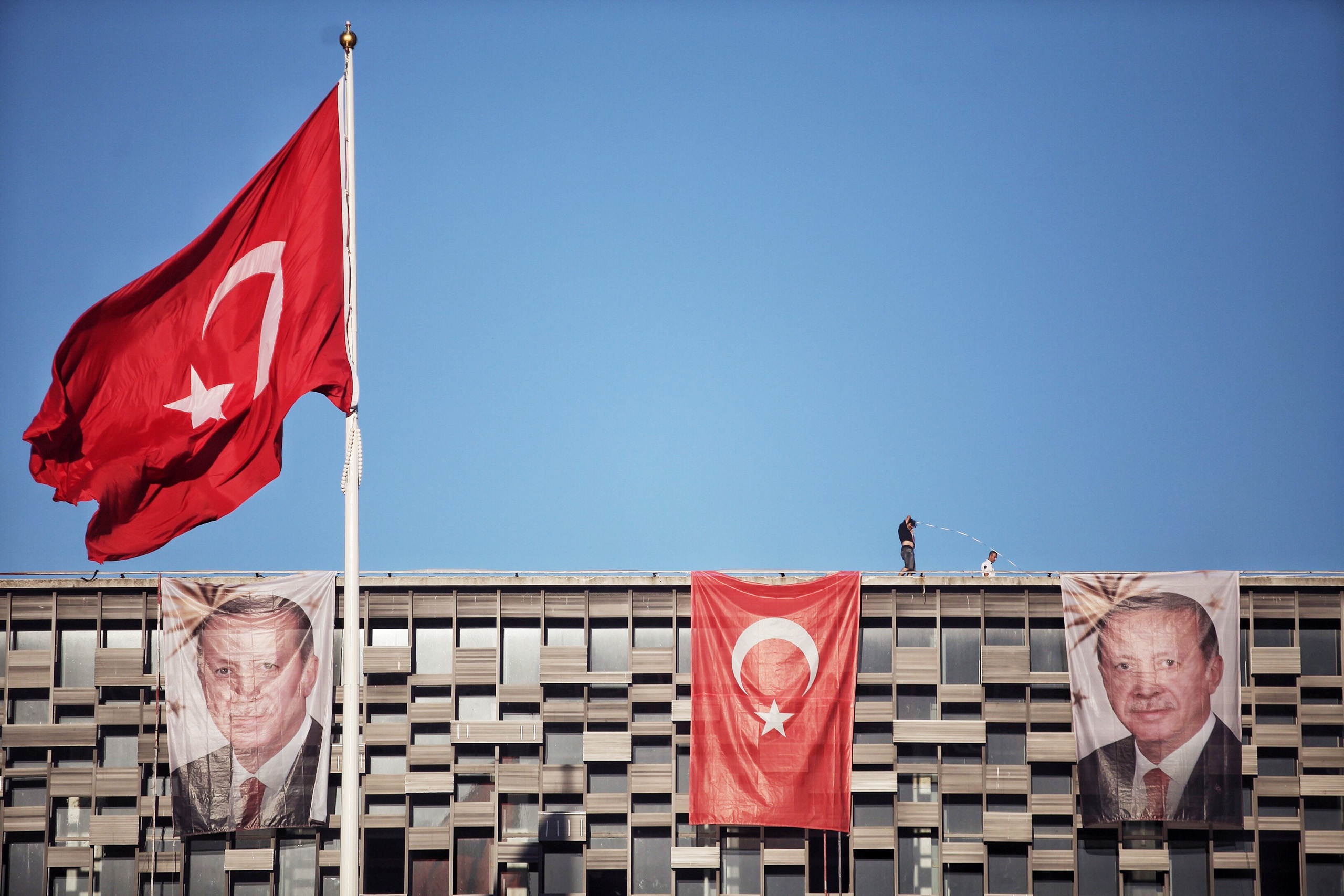 Posters of Turkey's President Recep Tayyip Erdogan and a Turkish flag hangs on Ataturk Cultural Center at Istanbul's central Taksim on July 19, 2016.
