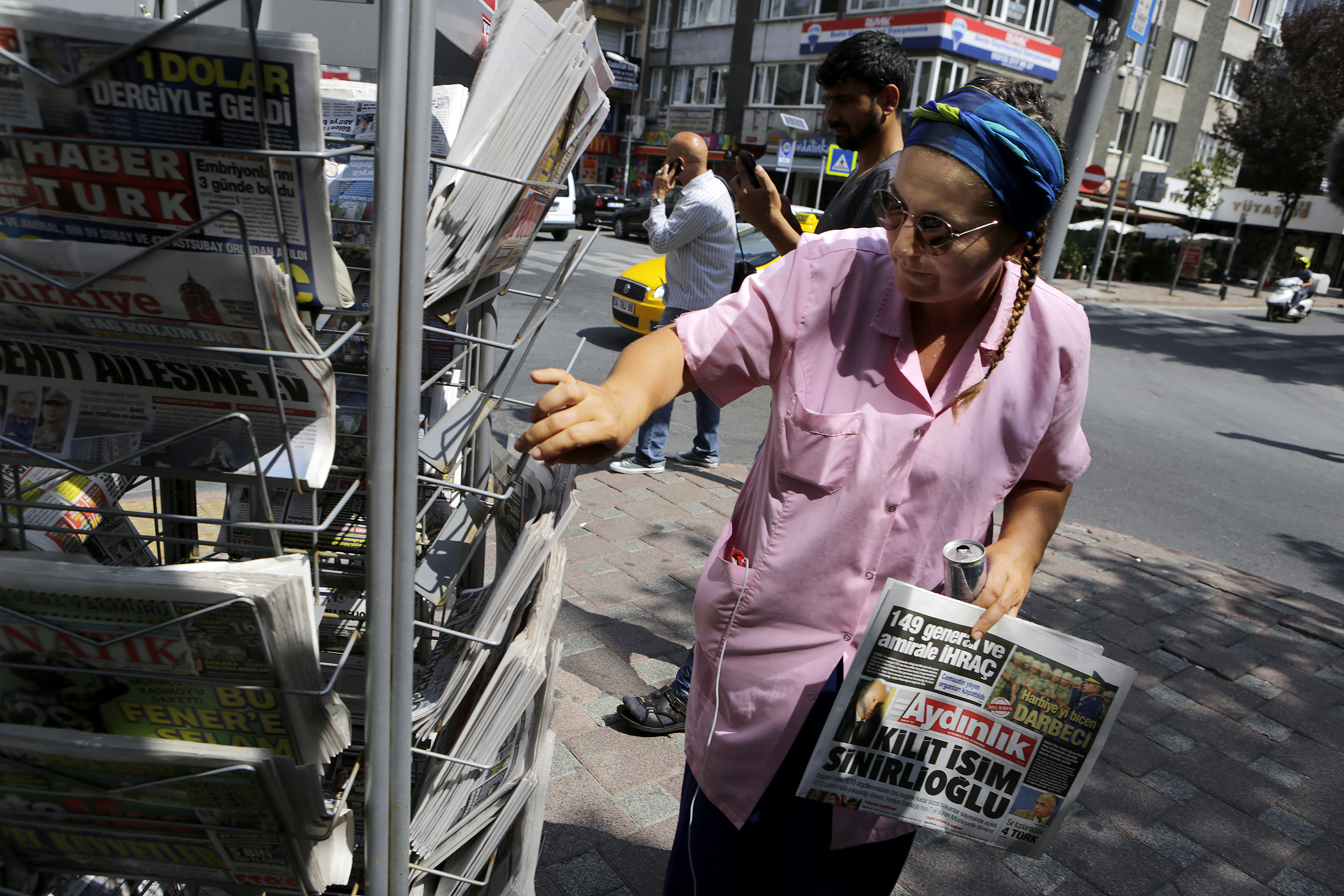 A woman buys a newspaper from a kiosk in Istanbul on July 28, 2016.
