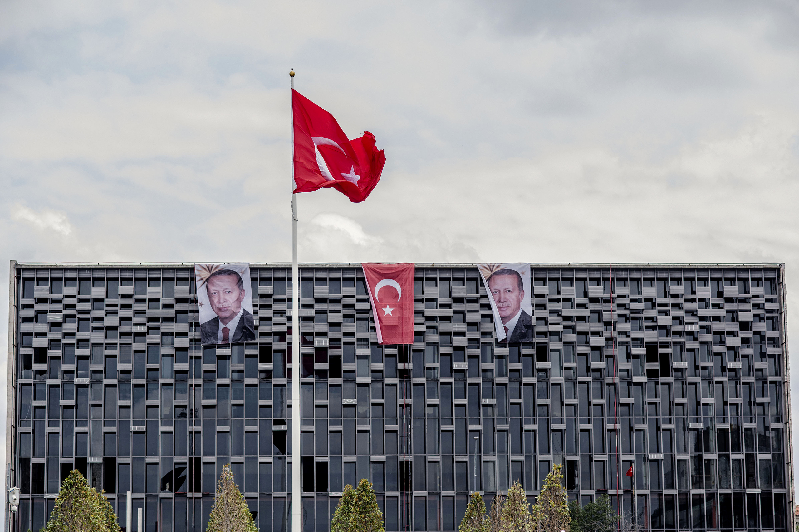 Banners with photographs of President Recep Tayyip Erdogan hang from the roof of a commercial building alongside the national flag in Istanbul, Turkey, on July 18, 2016.