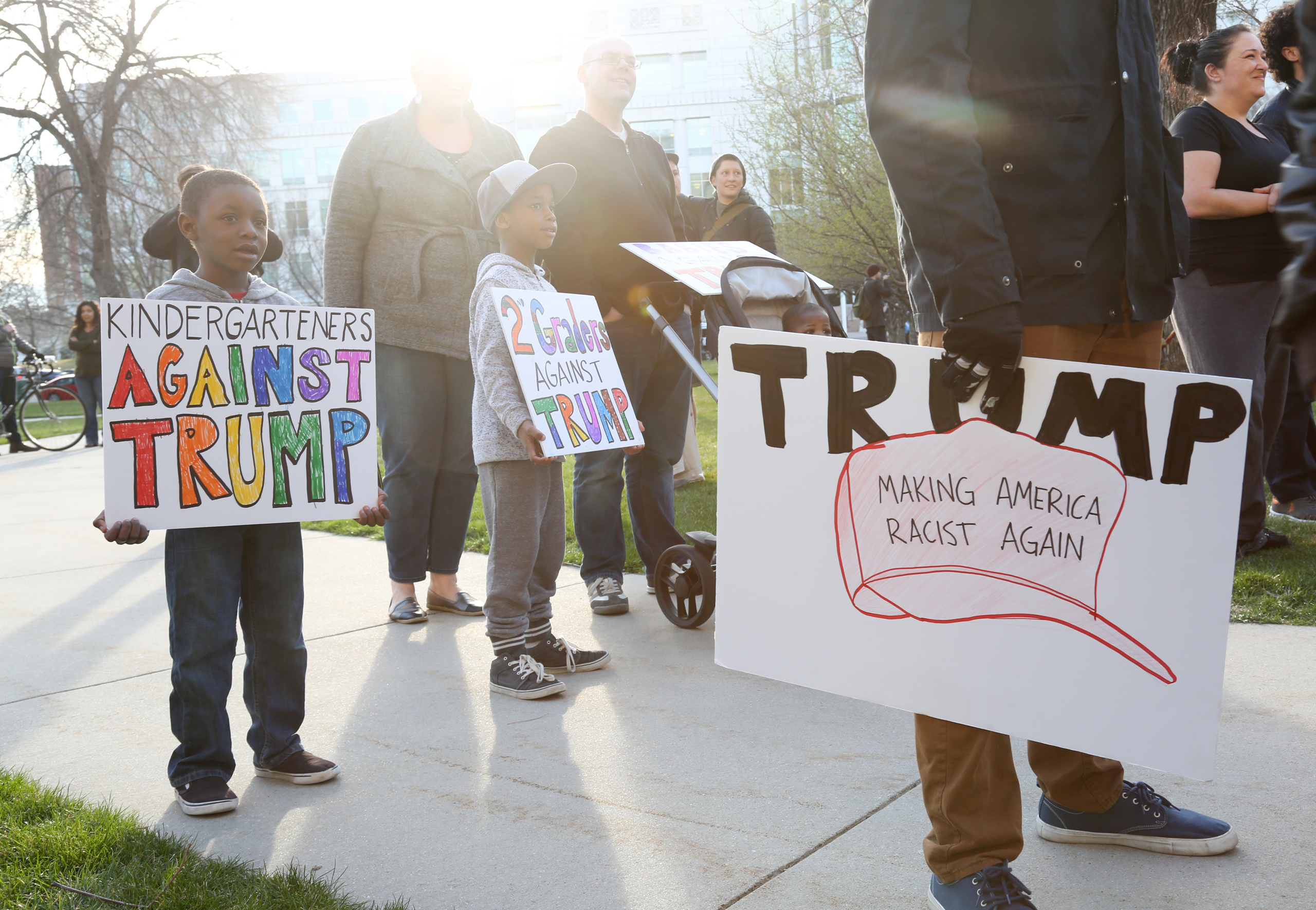 Brothers Noah, left and Owen Burket hold signs as they protest with their family at a rally outside the Infinity Events Center in Salt Lake City, where Republican Presidential candidate Donald Trump held a campaign rally on March 18, 2016.