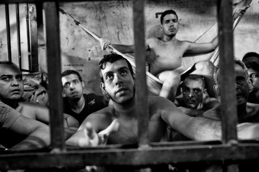 Prisoners inside a crowded cell at the Chacao municipal police station in eastern Caracas. There is no room to sit and prisoners take turns resting on sheets tied to bars like hammocks. Jails in Venezuela are seriously overcrowded with shortages of food and medicine. Because of the economic and political crisis, the number of prisoners grows daily as more Venezuelans are arrested for crimes, including mugging, kidnapping and murder, June 2016.