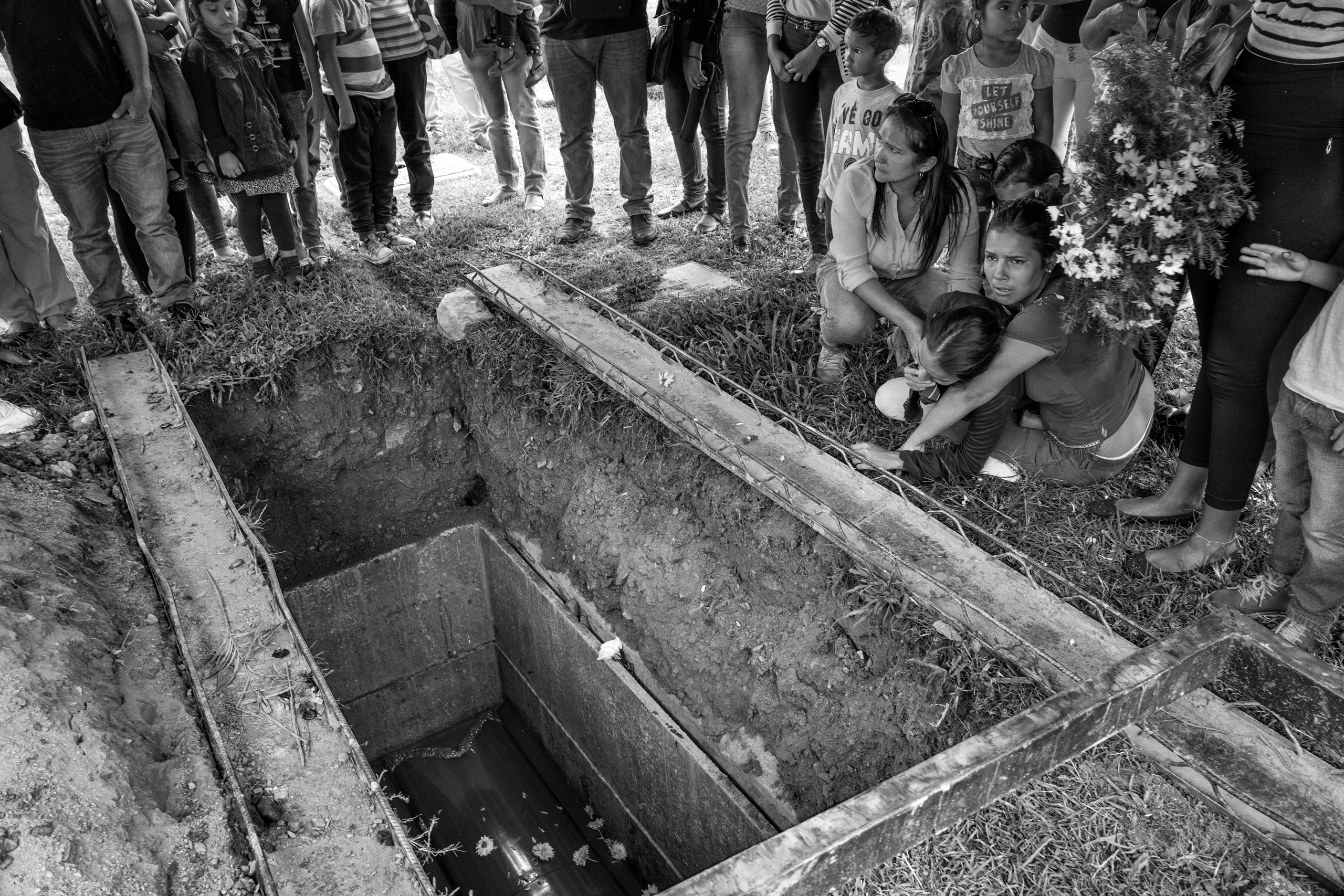 The wife of 25-year old Fredy Guerrero, who his family says was tortured and died while under police detention, cries at the grave of her husband, June 2016.