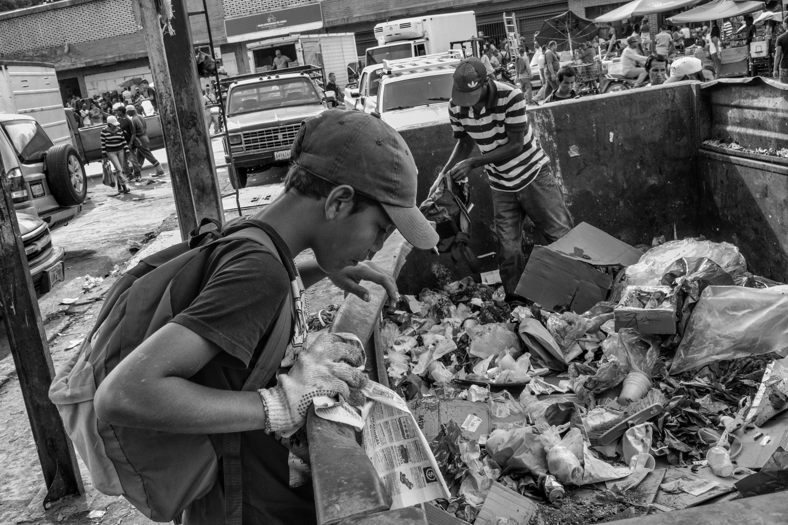 A bricklayer and his son look for food in a garbage dumpster in Caracas to take home to their family.  Because of the crisis in Venezuela, he has neither a job nor enough money to feed his family, June 2016.