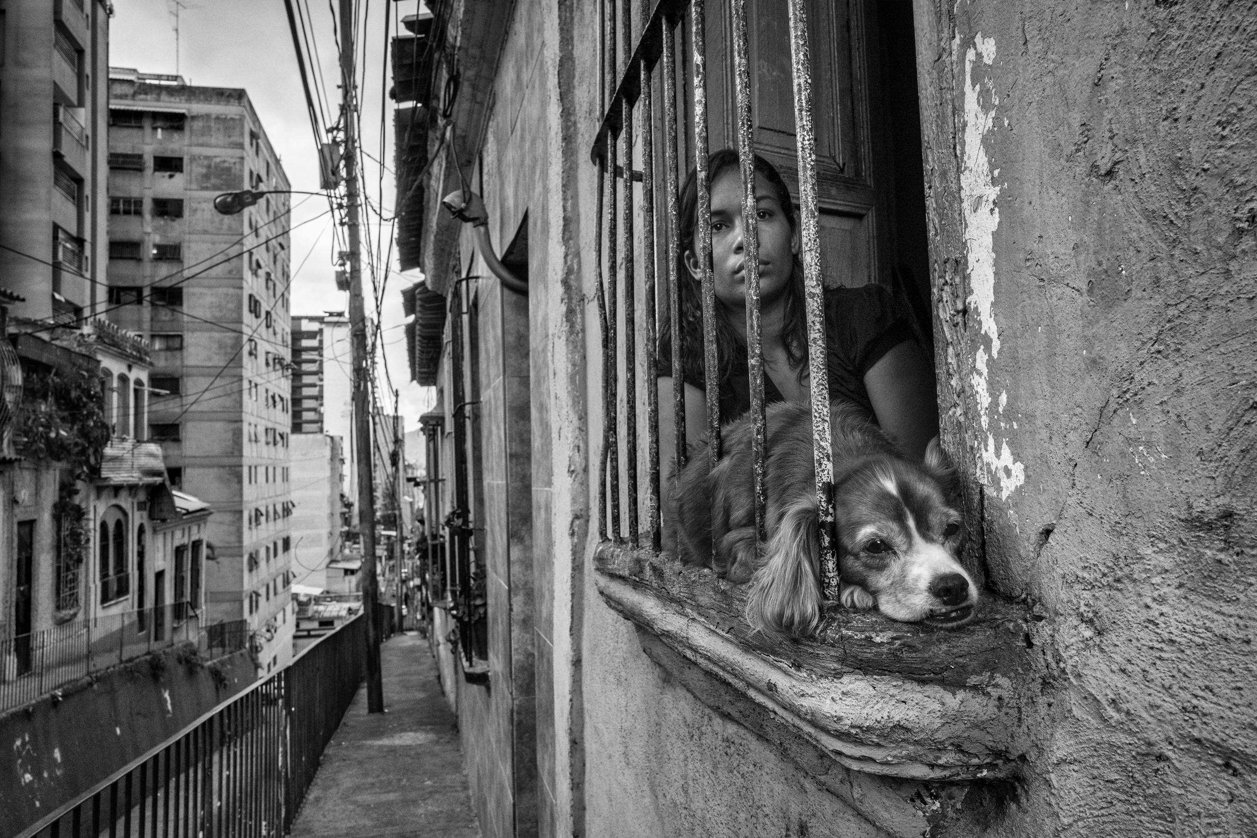 Bendiré looks out the window of her apartment in Caracas, which she shares with six other families.  After five p.m.,  she does not go outside fearing crime in the neighborhood, June 2016.