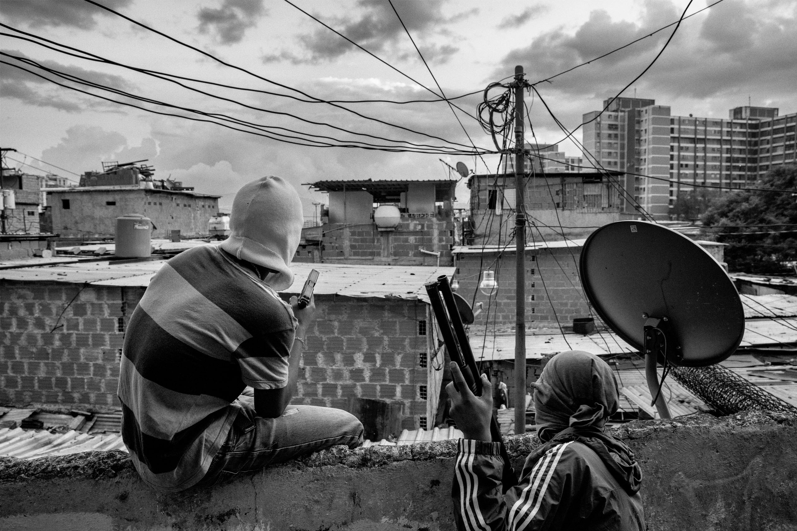 Members of a criminal gang lookout over their neighborhood in Caracas. Their faces are covered to avoid being identified by police, Caracas, Sept.  2015