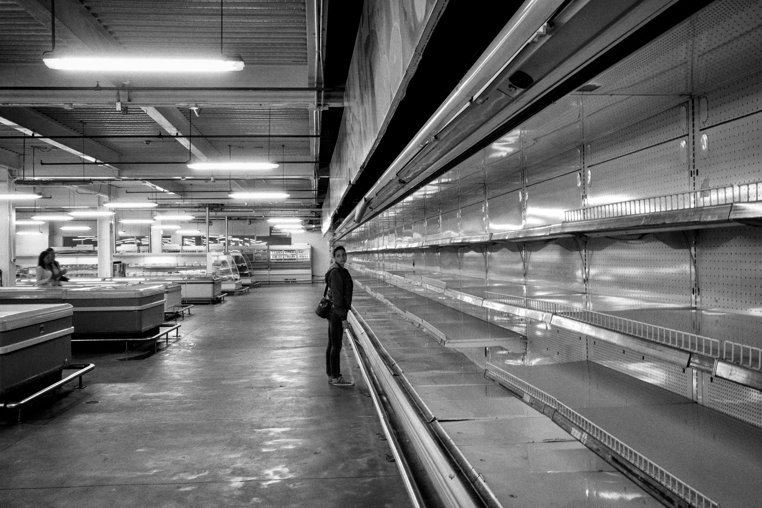 A woman stands before empty shelves in one of the major supermarkets in Caracas.  The severe political crisis has pushed the country a deep economic decline.  Sept. 2015.