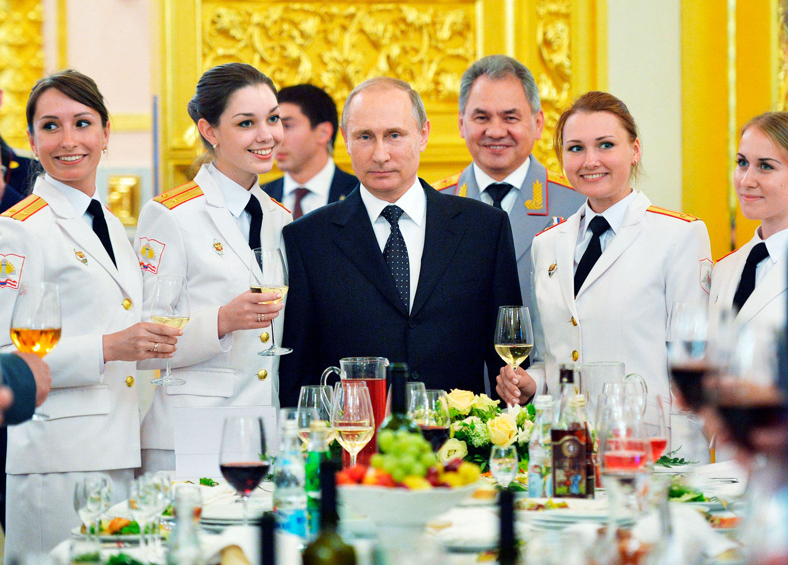 Putin, center, poses with female graduates of military colleges at the Kremlin on June 28