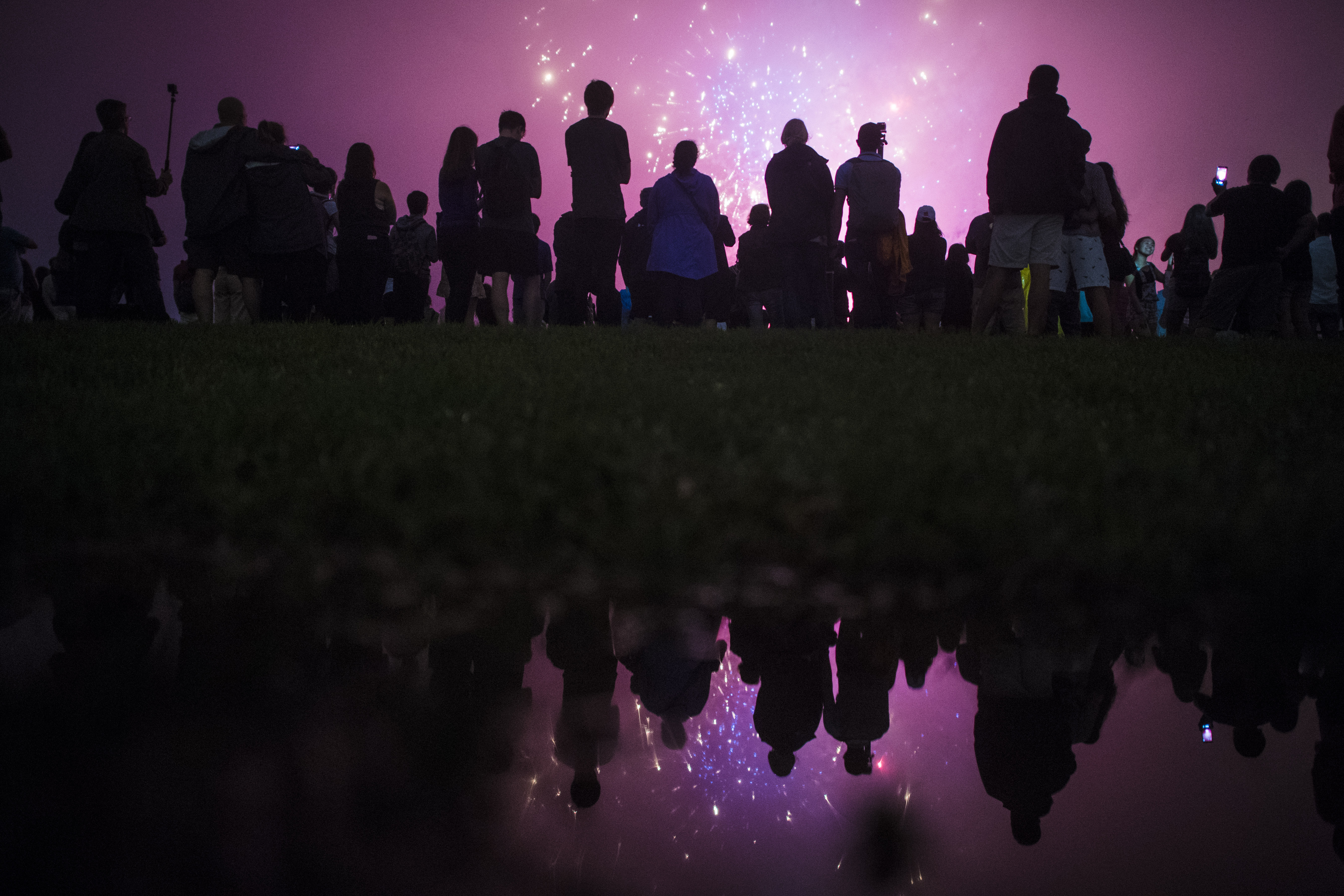 WASHINGTON, DC - JULY 4: Patrons, reflected in a rain puddle, watch near the Washington Monument as the Independence Day fireworks go off on the National Mall in Washington, DC on Monday July 04, 2016. (Photo by Jabin Botsford/The Washington Post via Getty Images)