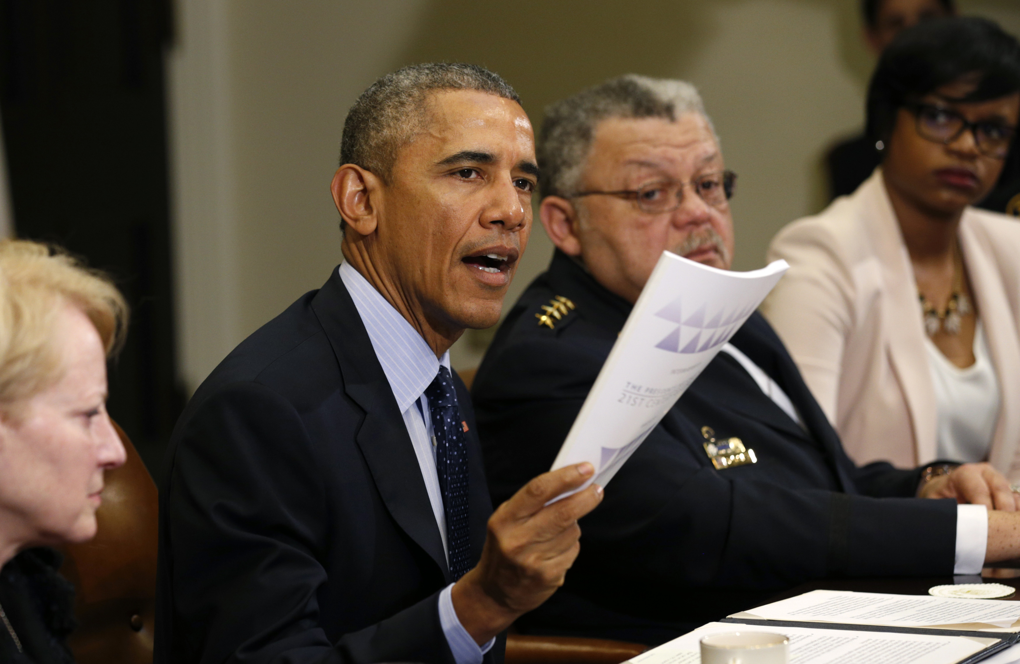President Barack Obama holds up a copy of the report by the Task Force on 21st Century Policing at the White House in Washington, March 2, 2015.