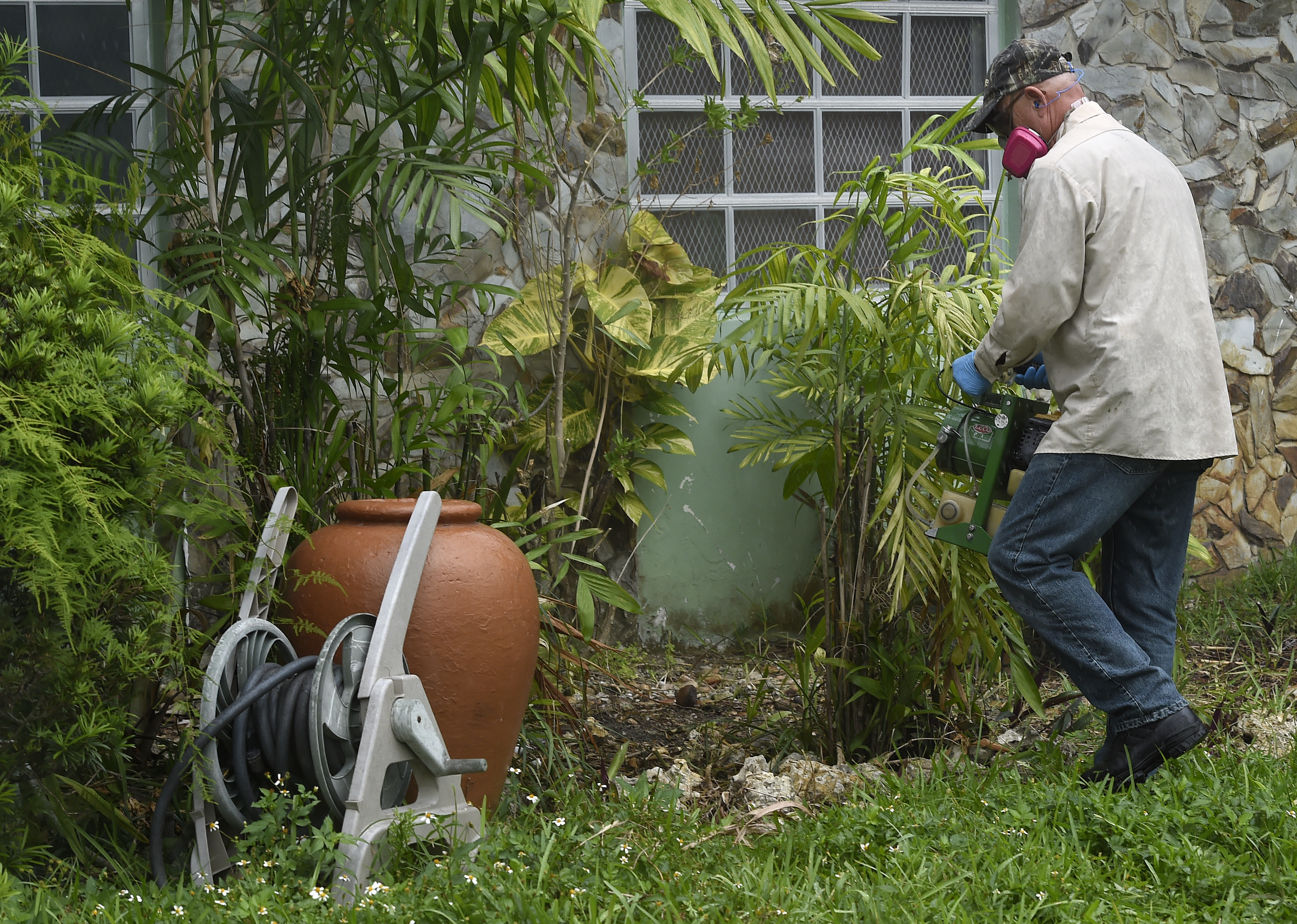 Miami-Dade mosquito control worker Carlos Vargas sprays to eradicate the Aedes aegypti mosquito larvae at a home in Miami, June 8, 2016.