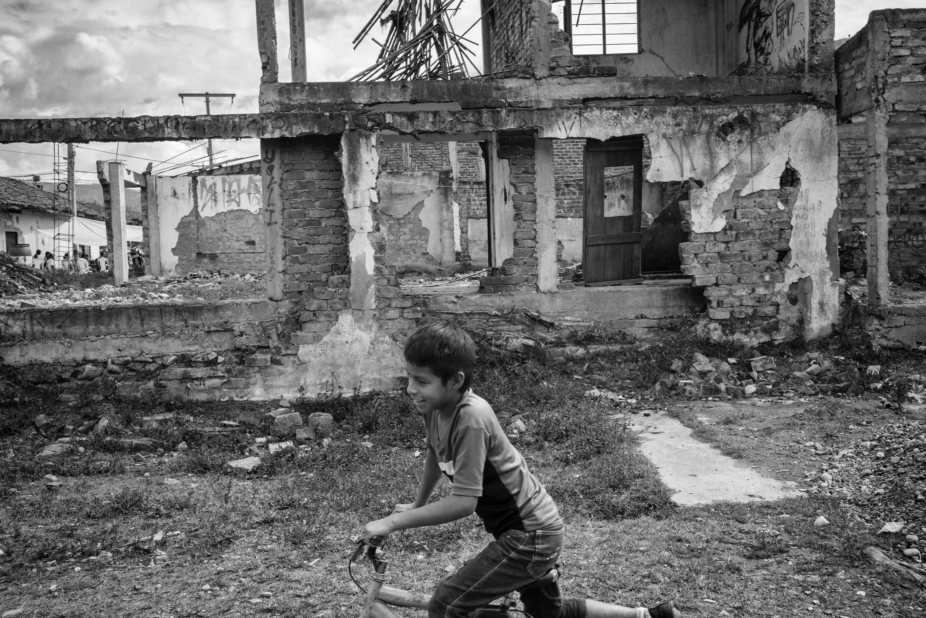 A child rides a bicycle in front of                                   the ruins of a house destroyed in an attack by FARC in the com- munity of Toribio, Colombia. Many regions of Colombia have lived for more than 52 years under FARC's control. A Peace agreement reached in Havana, Cuba on Aug. 24, 2016 raised many doubts and fears among civilians about the future that awaits these communities neglected by the state, Cauca, Colombia, July 2016.