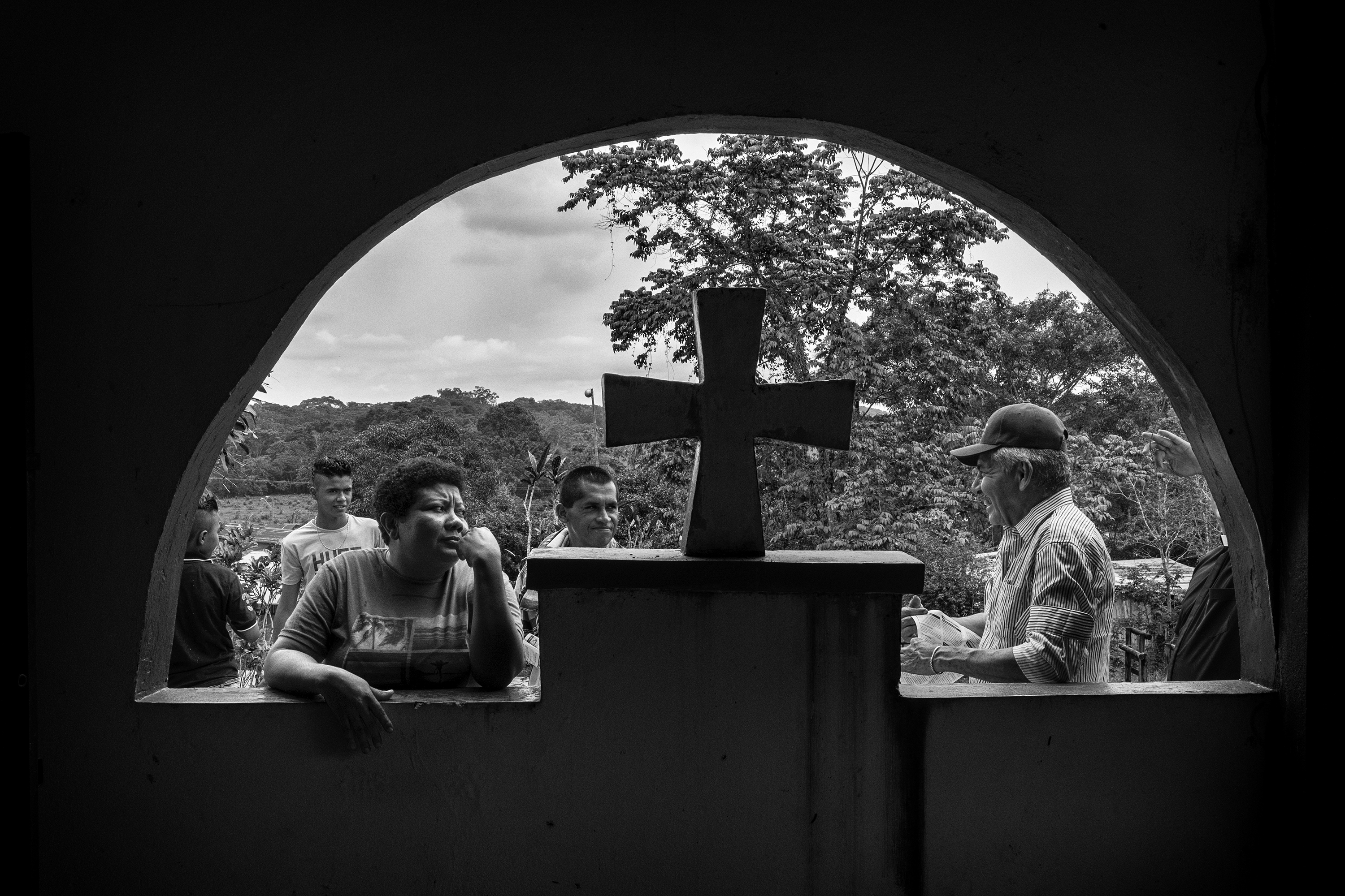 A group of civilians wait for a mass in the village of Puerto Camelias, Caqueta, Colombia, which is one of the villages under FARC guerrilla control,  Caqueta region, March, 2016.