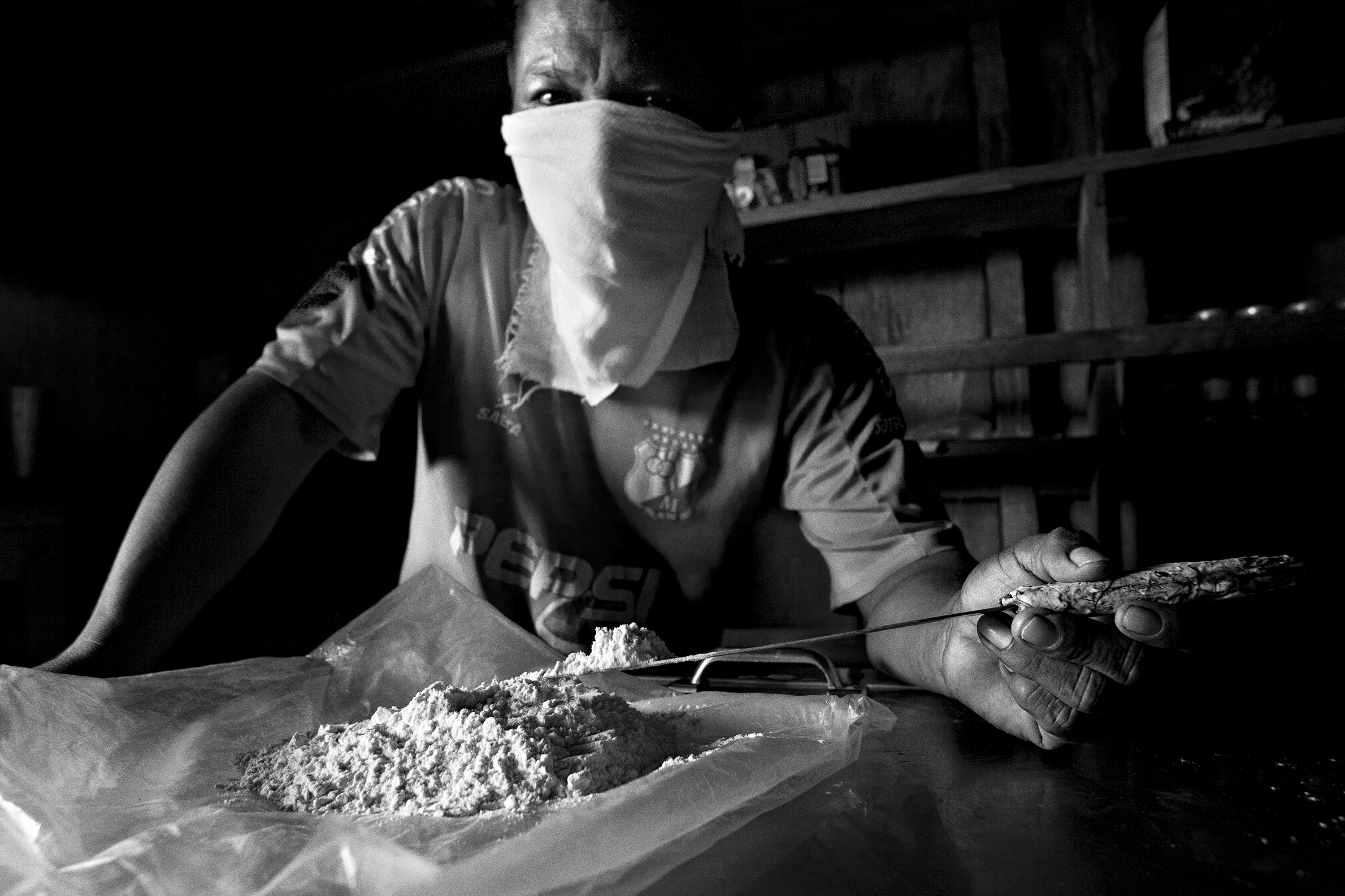 A local narcotics dealer holds up pure cocaine. All the different armed groups who take part in the conflict benefit from this market, with coca cultivation being the main source of income for families in this region, Colombia, Nov.  2007.