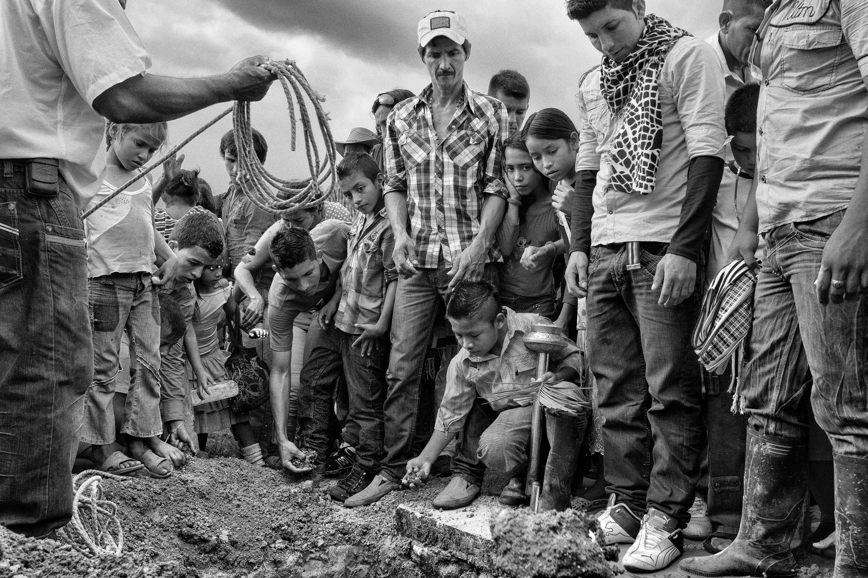 Family and friends gather for the funeral of 18-year old Benjamin, who died during a fight with guerrillas, Nov. 2013, La Unión Peneya, Caqueta, Colombia.   FARC guerrillas are not the only armed group which operate in Colombia. The ELN guerrilla and paramilitary groups also control vast areas of territory, applying their own laws and acting as the only authority.