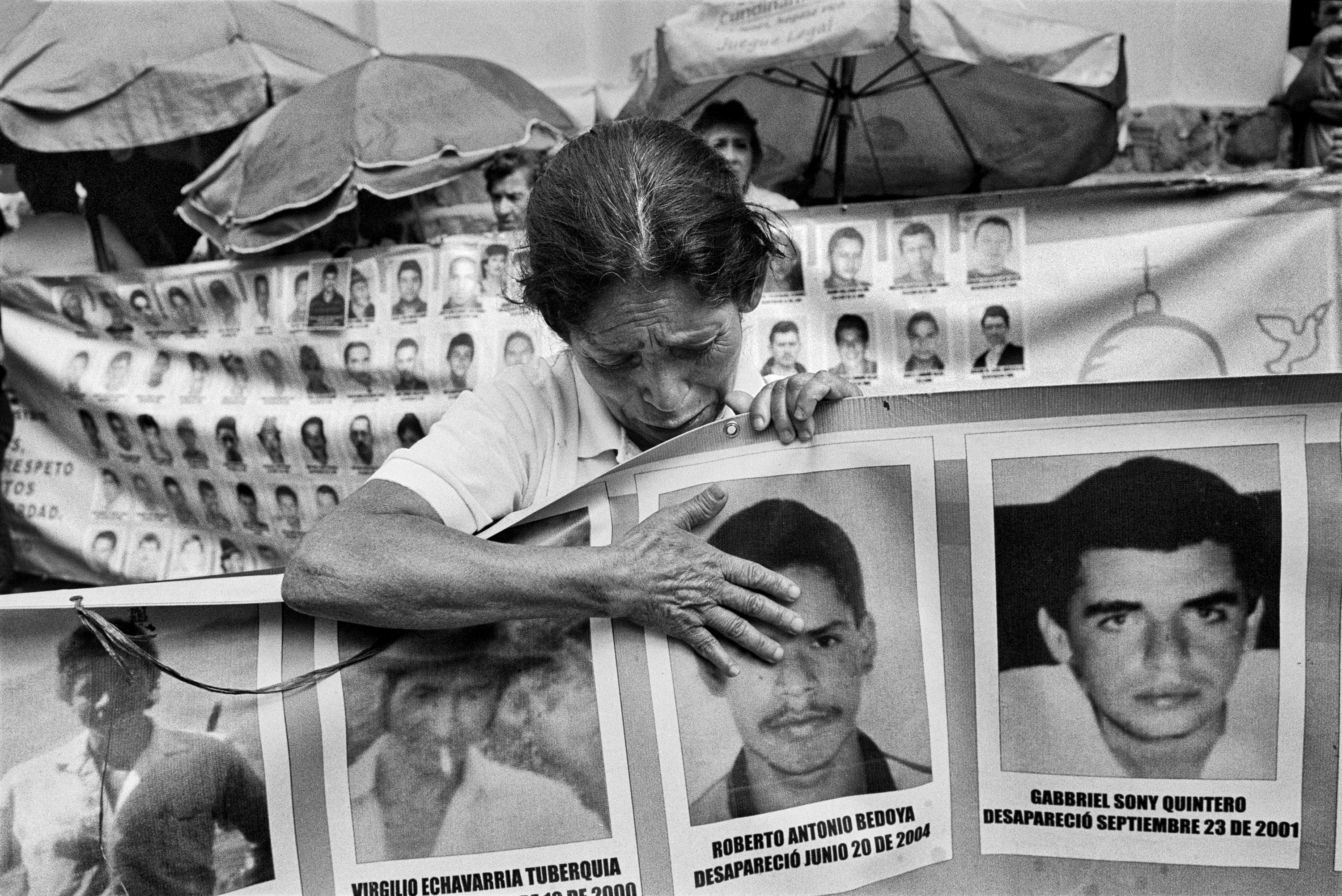 A mother cries to a picture of her missing son during a vigil in the Center of Medellin, Colombia, Feb. 2015. Every Friday, the association of mothers of the Candelaria organizes a vigil to remember and demand the return of their missing relatives. There are more than 96,000 people missing in Colombia.