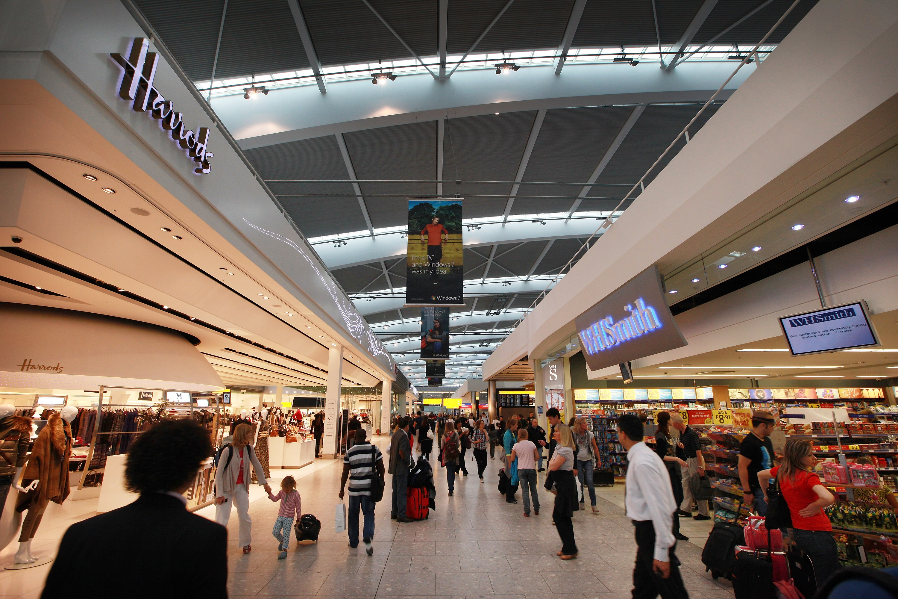 Passengers walk  through the shopping area at terminal five at Heathrow airport on August 27, 2010 in London, England.