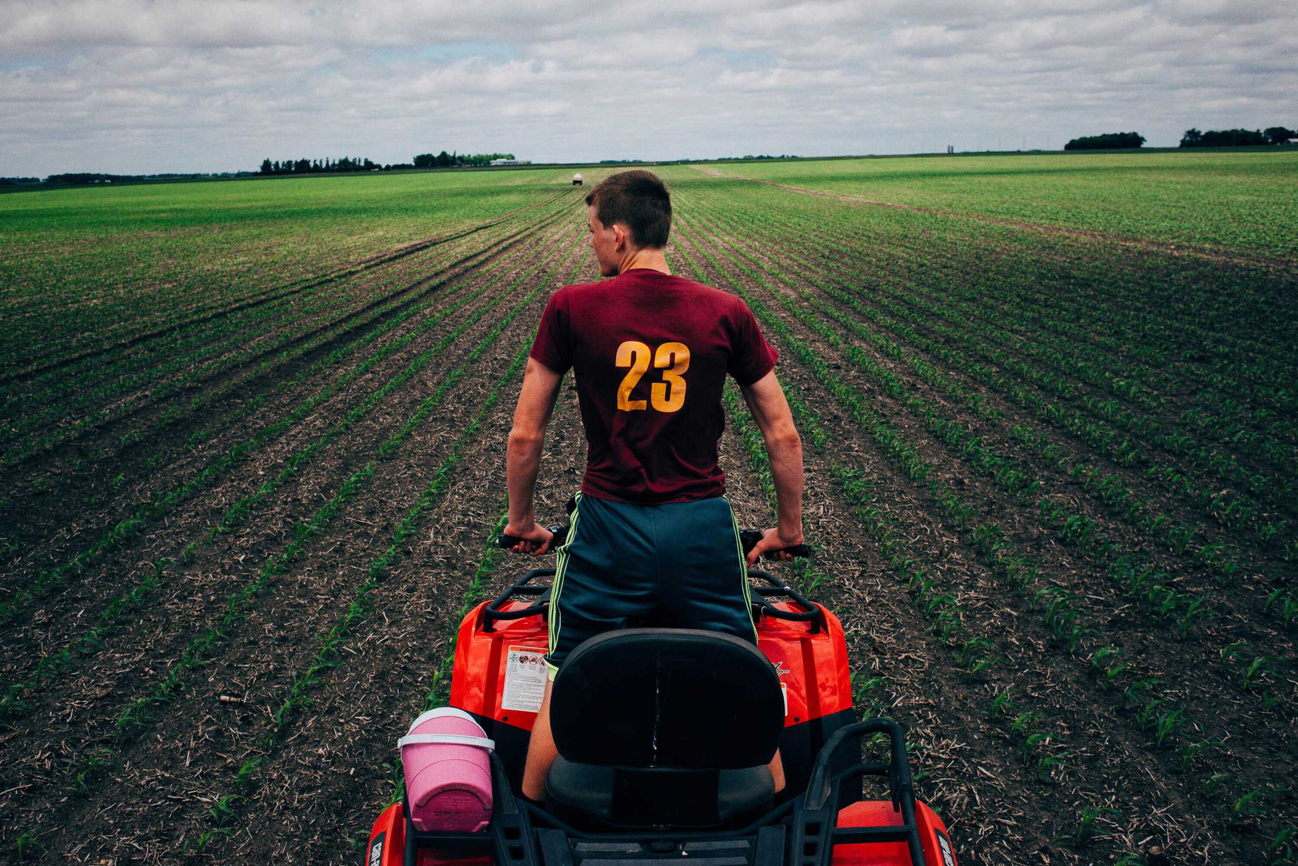 Ben White looks for rocks while driving an ATV through a field owned in Springfield Township, Minnesota on June 1, 2016.