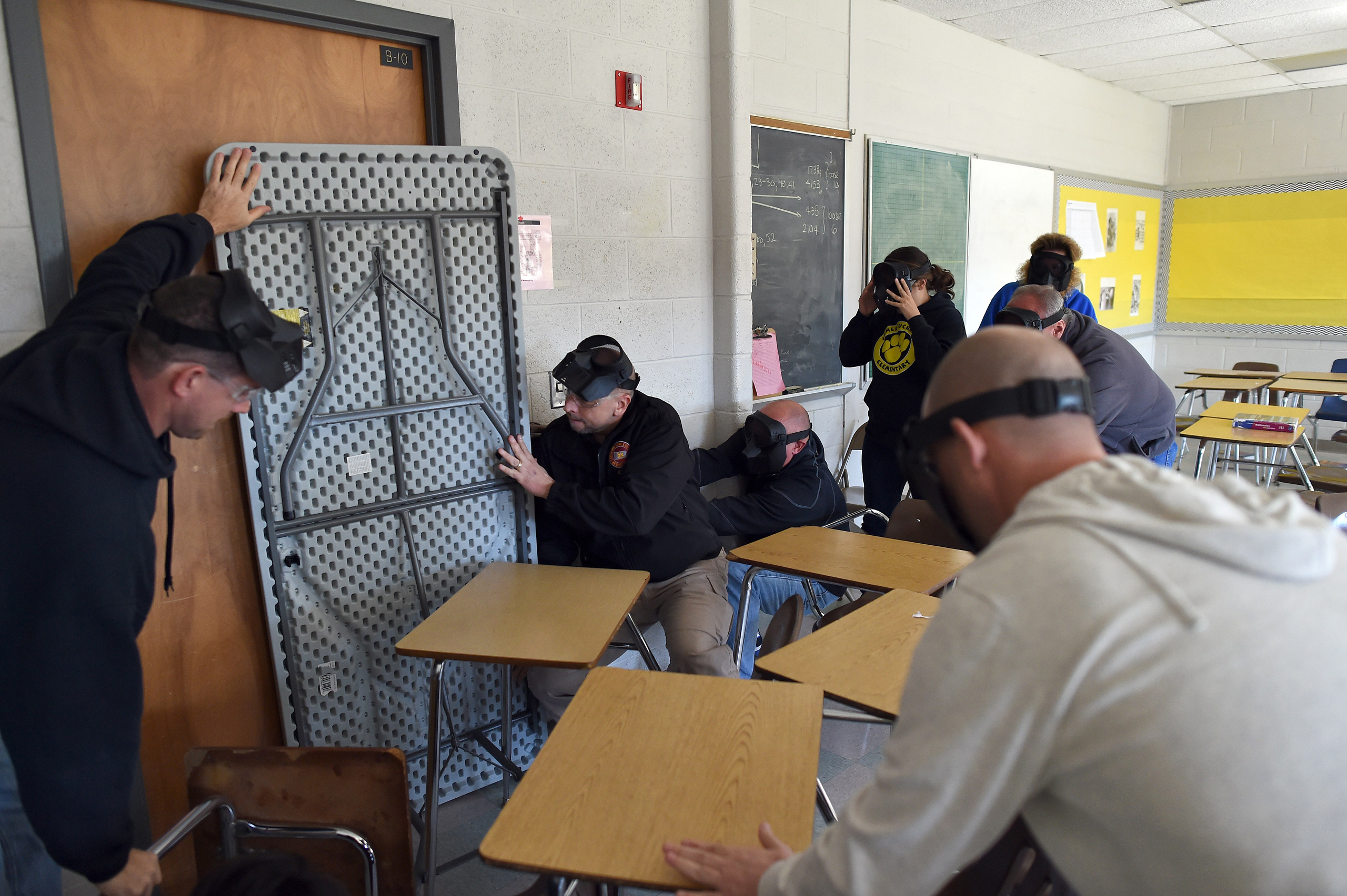Participants barricade a door of a classroom to block an  active shooter  during ALICE (Alert, Lockdown, Inform, Counter and Evacuate) training at the Harry S. Truman High School in Levittown, Pennsylvania, on Nov. 3, 2015.