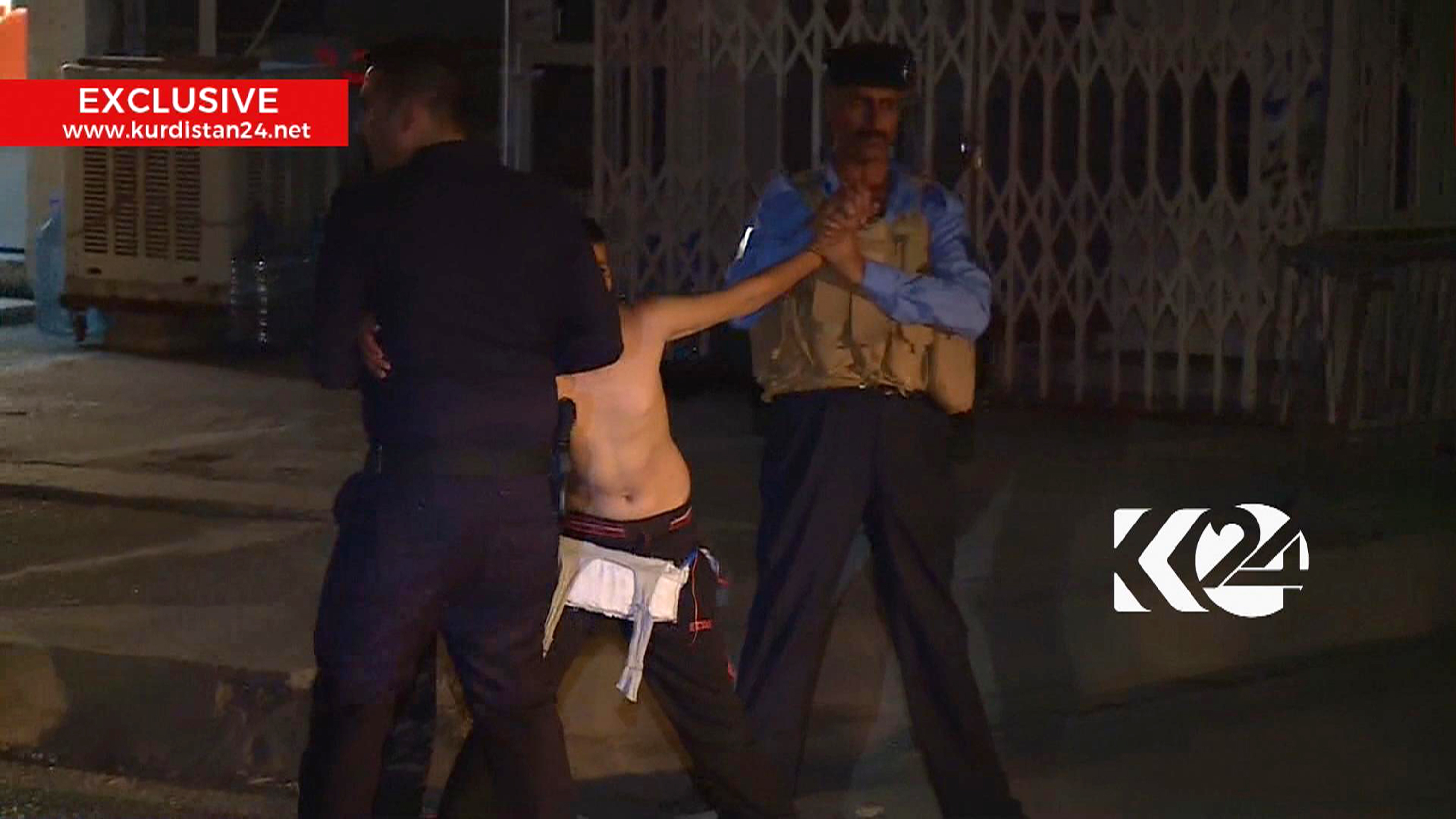 This still taken from local TV footage shows a child being restrained by security forces, holding his arms out-stretched as another man cuts off a belt of explosives, in Kirkuk, Iraq.  (Kurdistan 24 TV news via AP)