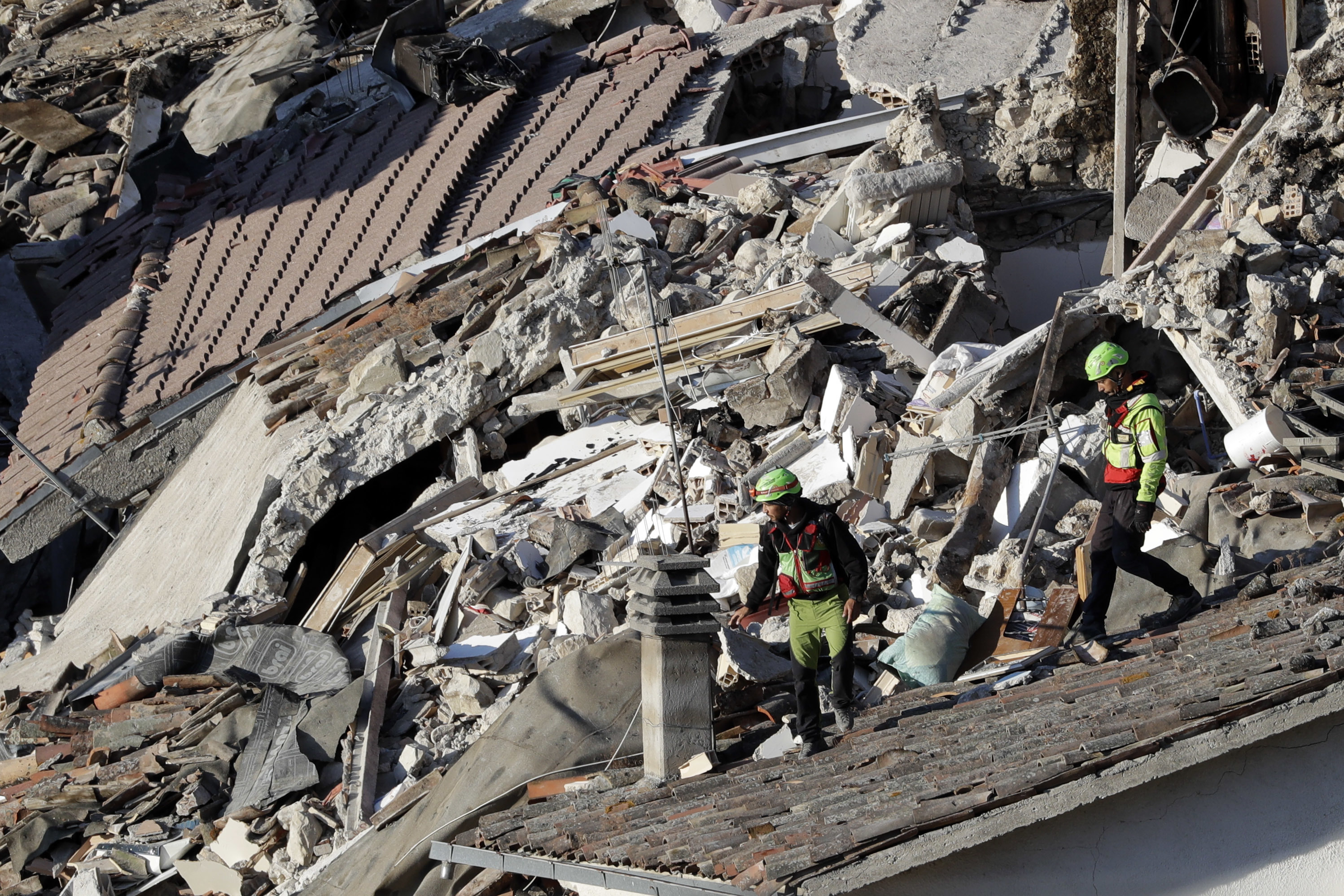 Rescuers make their way through destroyed houses following an earthquake in Pescara Del Tronto, central Italy, Aug. 25, 2016.