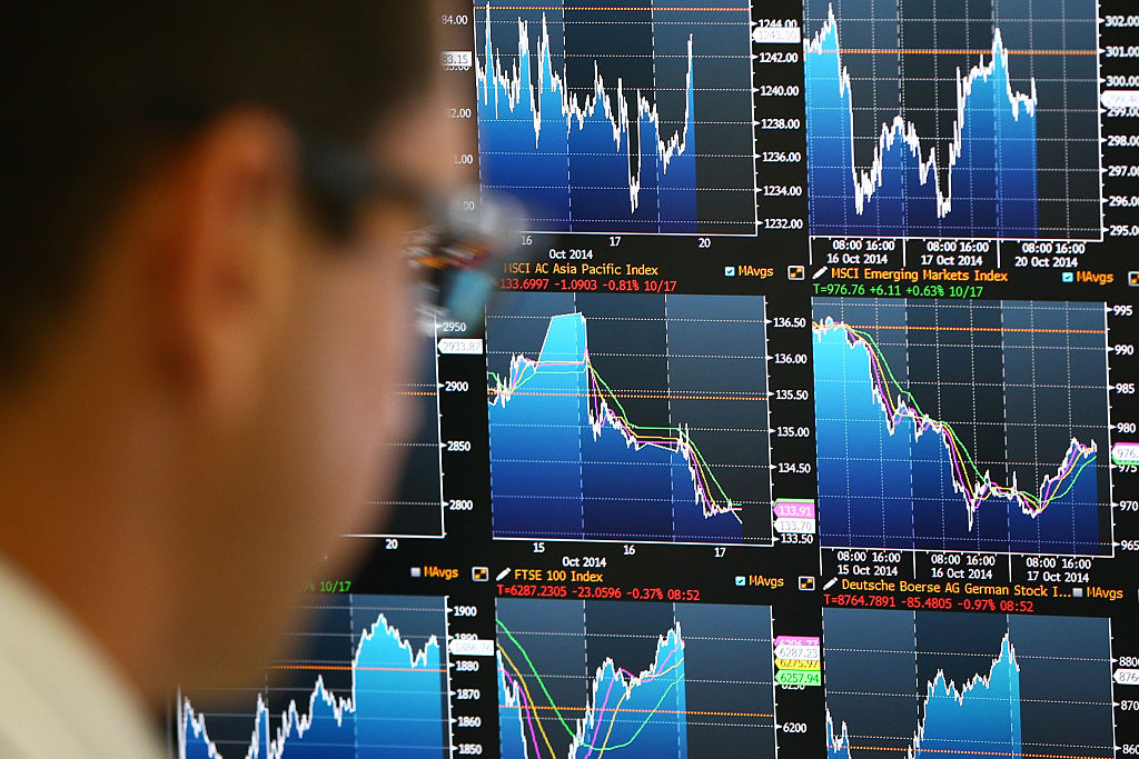 An employee views trading screens at the offices of Panmure Gordon and Co in London  on Oct. 20, 2014.
