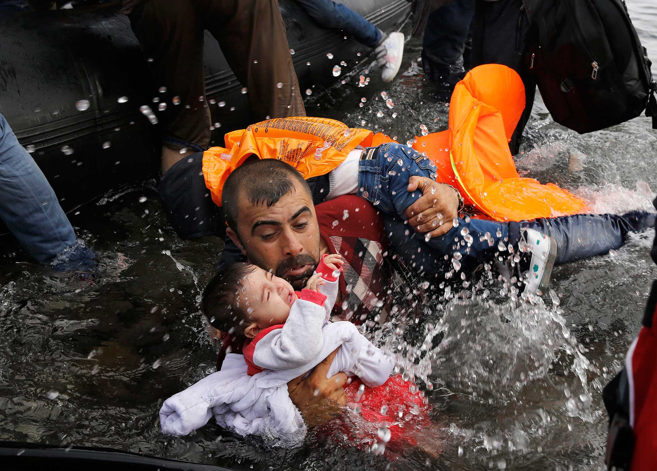 A Syrian with his two children struggling to disembark after crossing from Turkey. Island of Lesbos, Sept. 24, 2015.