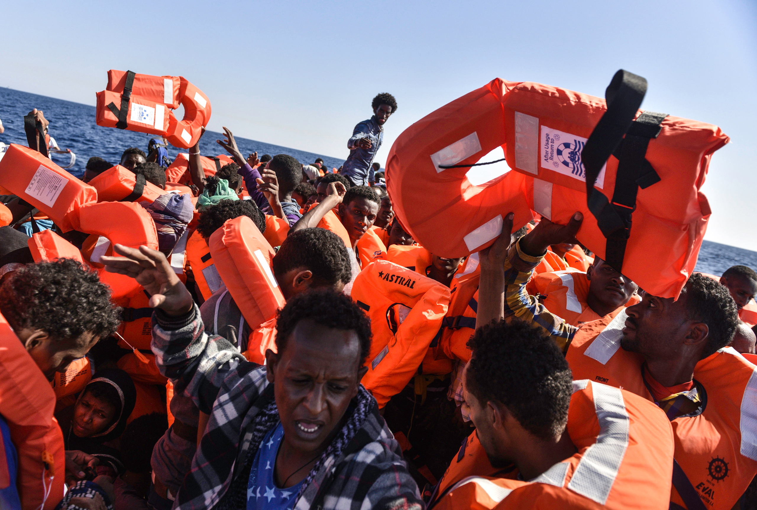 Migrants pass the life jackets being handed out by the search-and-rescue teams with Médecins Sans Frontières and SOS Méditerranée off the coast of Libya, Aug. 21, 2016.