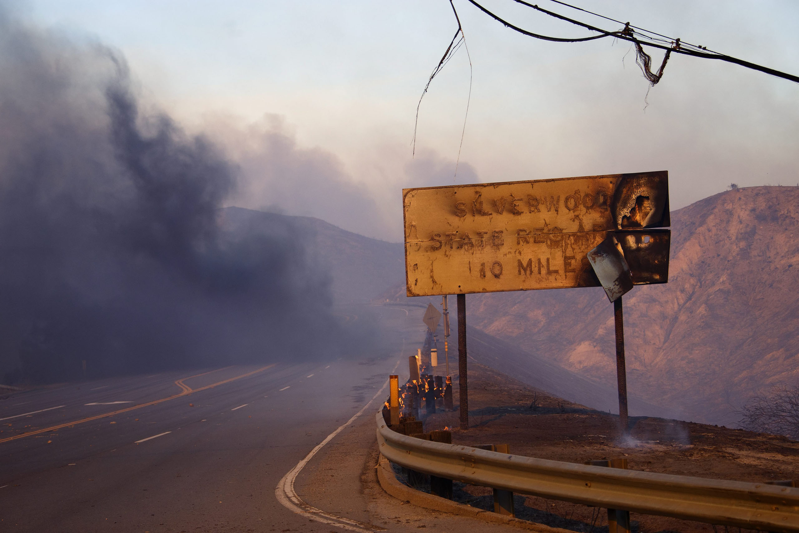 A melted sign shows the damage after a wildfire swept through Cajon Junction, Calif., Aug. 16, 2016.