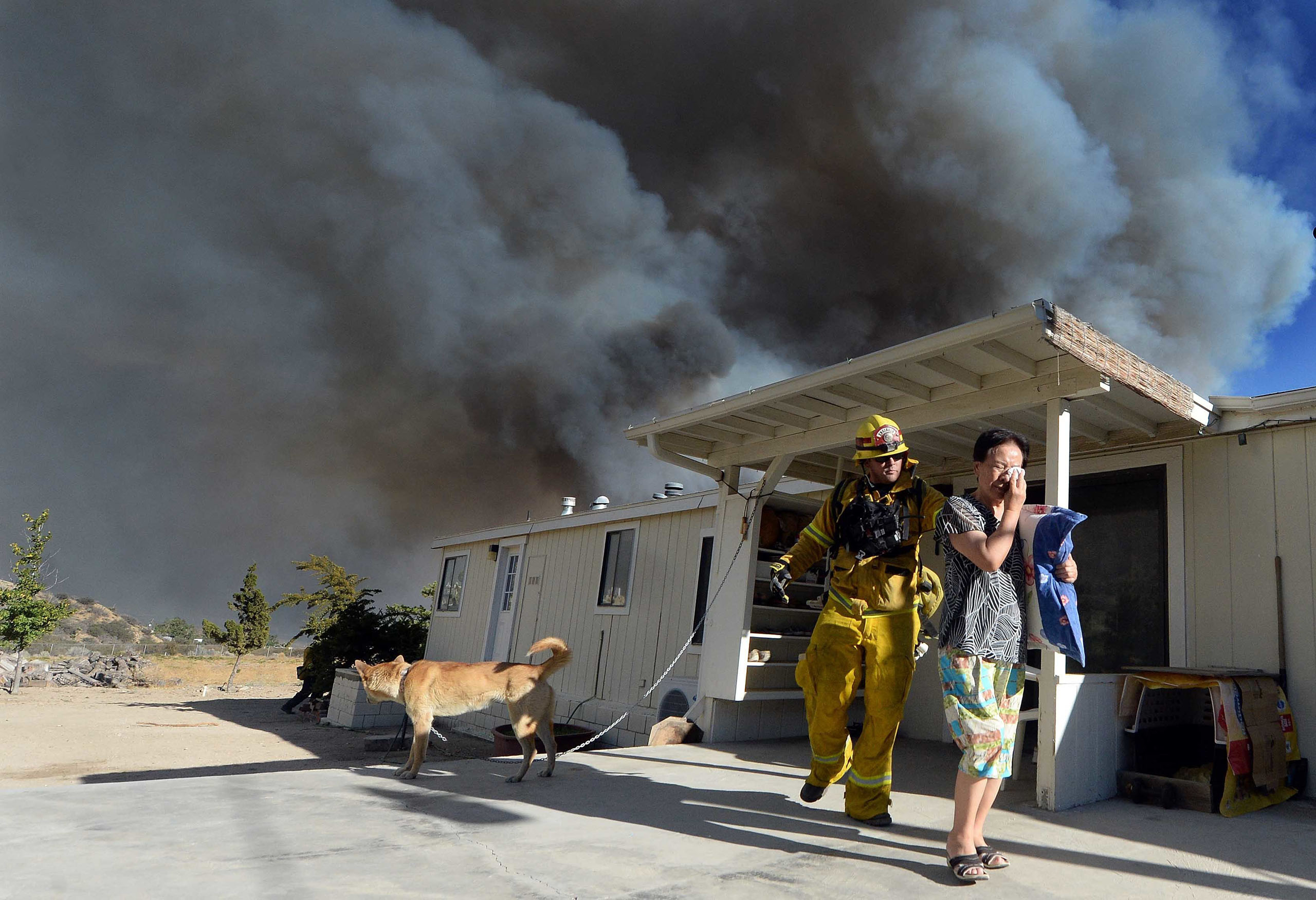 San Bernardino firefighter, engineer and paramedic Jeremy Pendergraft helps evacuate a couple from their home as the wildfire off of Highway 138 quickly approaches in San Bernardino, Calif., Aug. 16, 2016.