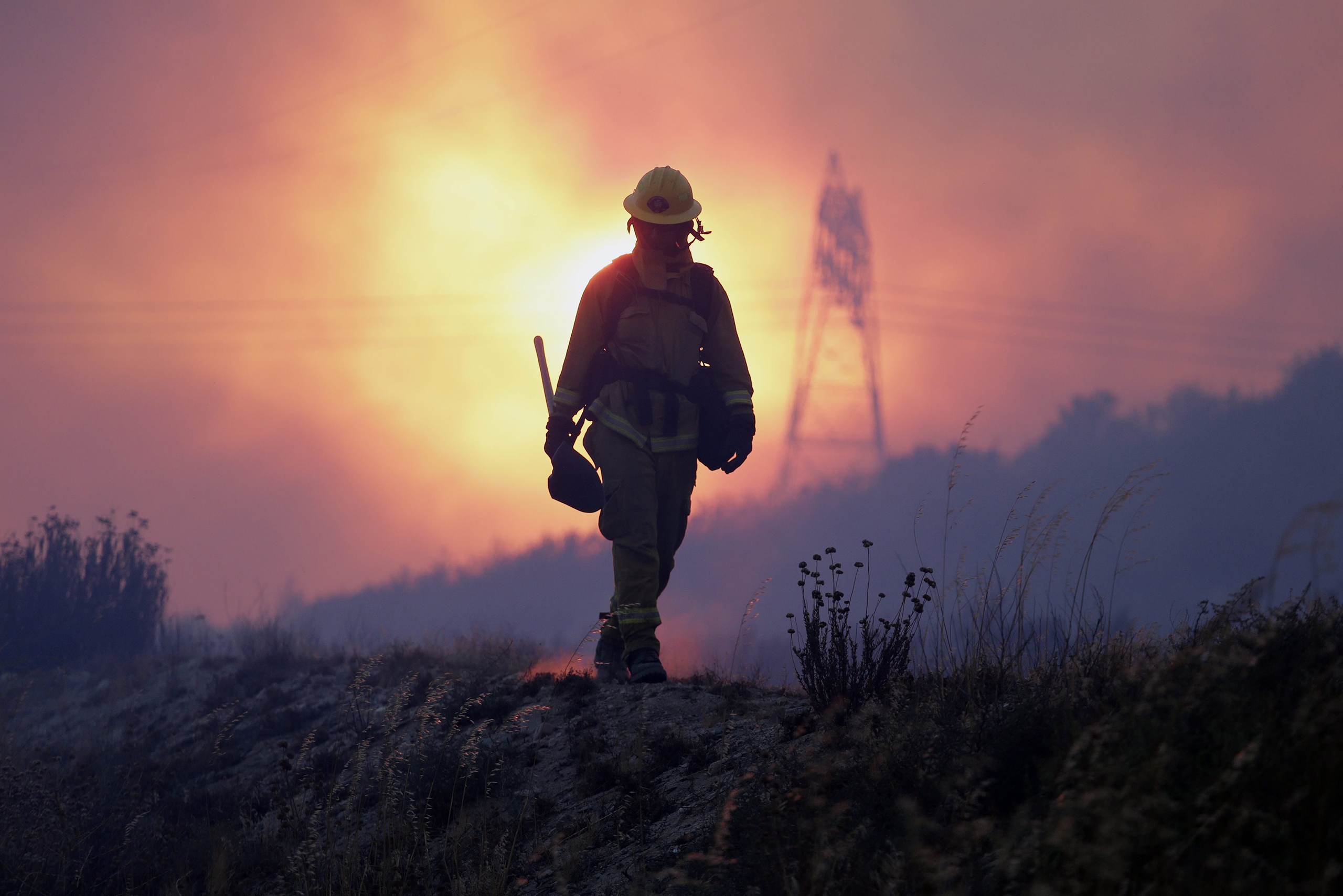 A firefighter keeps an eye on the Blue Cut fire line, north of Los Angeles, Calif, Aug. 16, 2016.