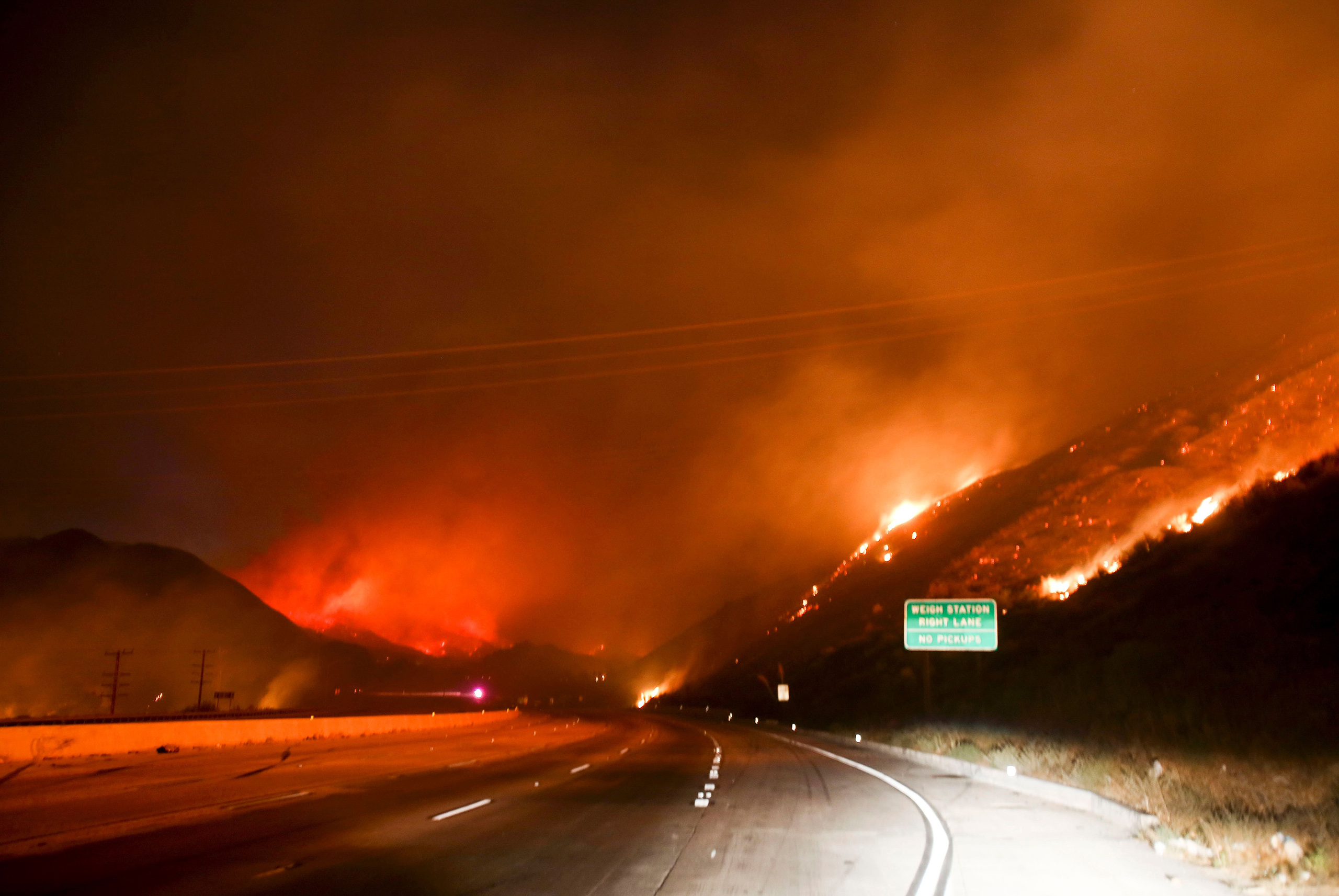 Flames burn next to Interstate 15 as the Blue Cut wildfire rages near Cajon Pass, north of San Bernardino, Calif., Aug. 16, 2016.