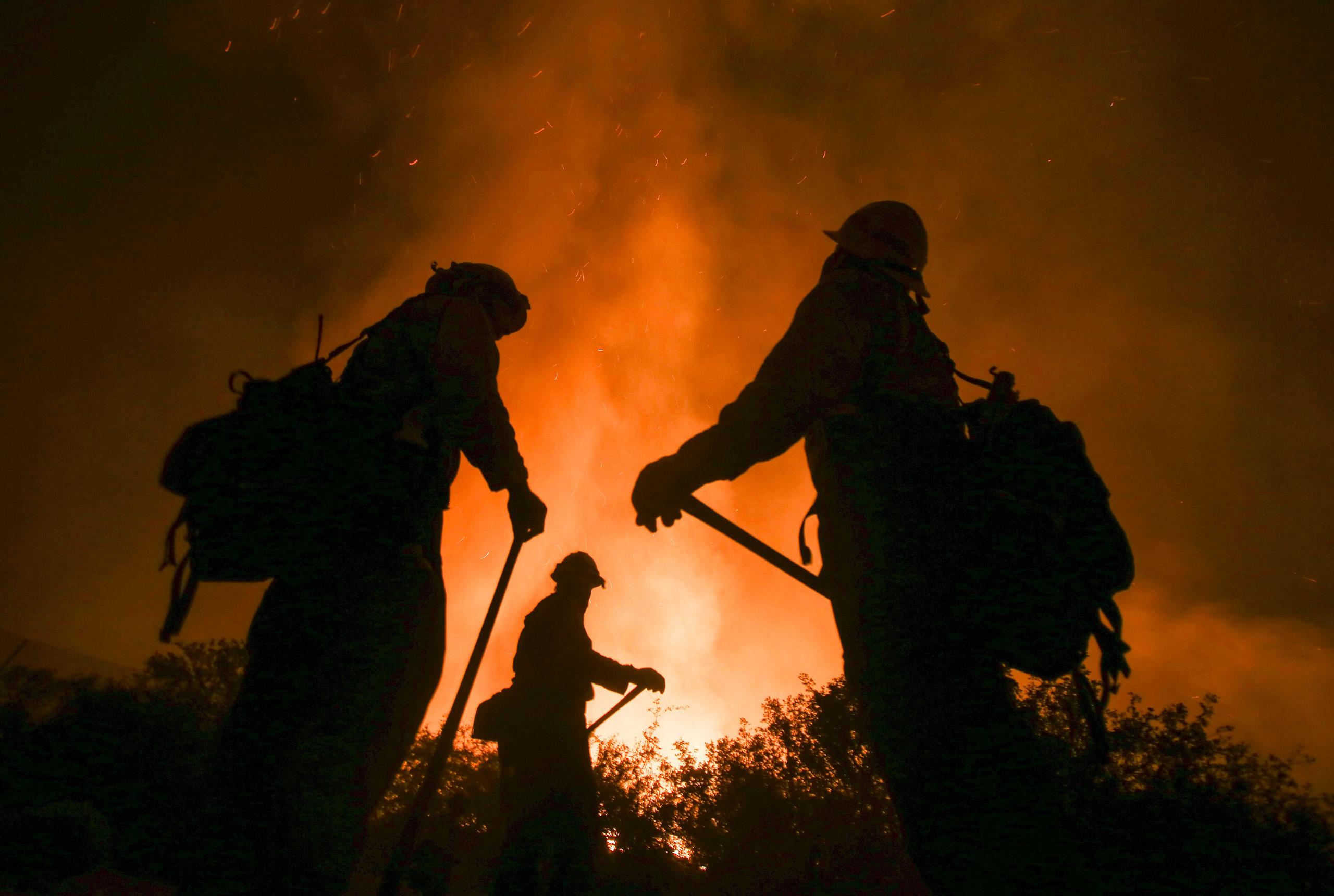 Firefighters battle the Blue Cut wildfire near Cajon Pass, north of San Bernardino, Calif., Aug. 16, 2016.