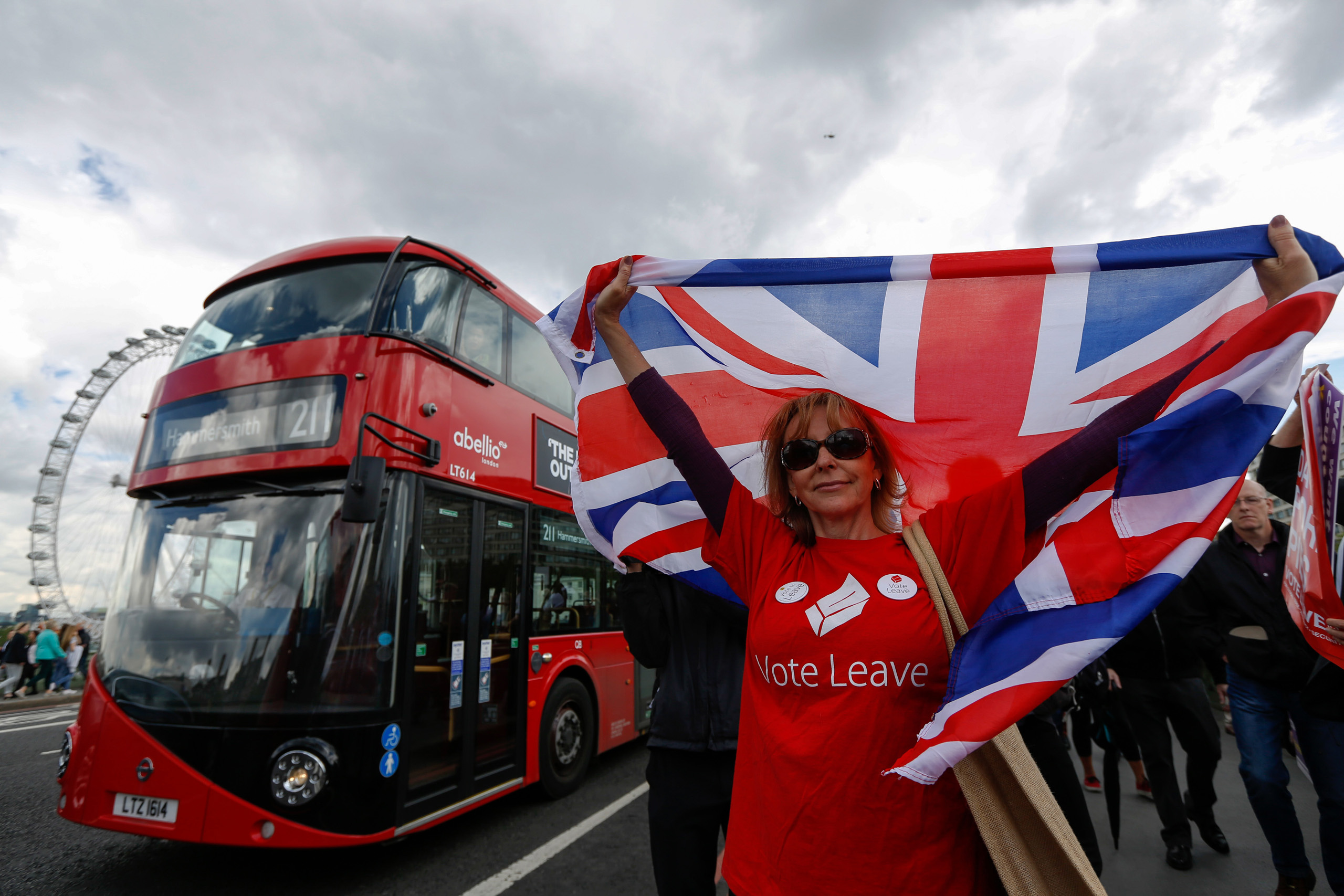 A campaigner wearing a Vote Leave T-shirt and holding a British Union Flag, also known as a Union Jack, stands on a Westminster Bridge near the Houses of Parliament in London on  June 15, 2016