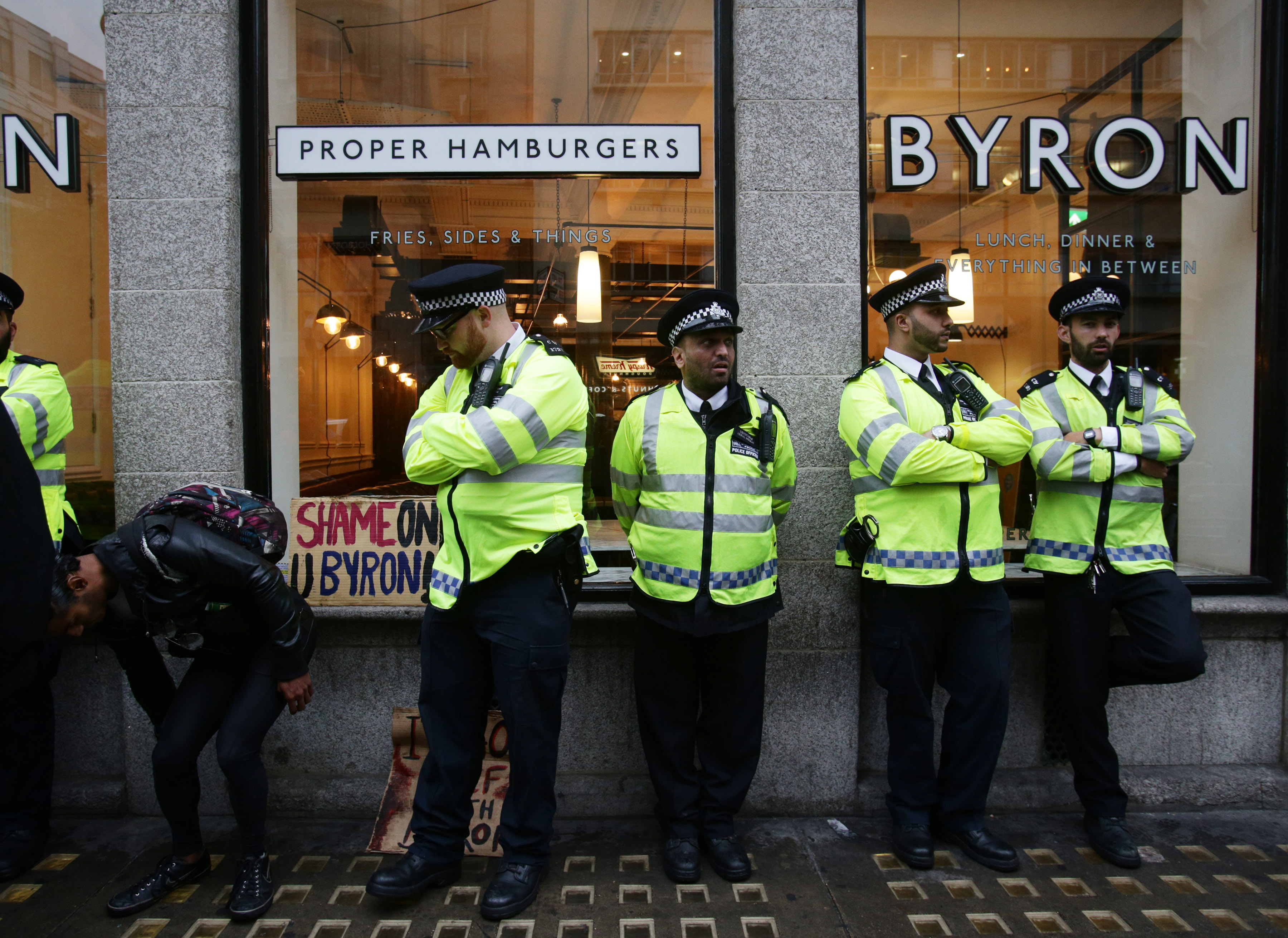 Byron workers held. Police officers stand outside a Byron restaurant in Holborn, central London, as people protest after dozens of workers at the burger chain were arrested in a swoop by immigration officials, on Monday August 1, 2016