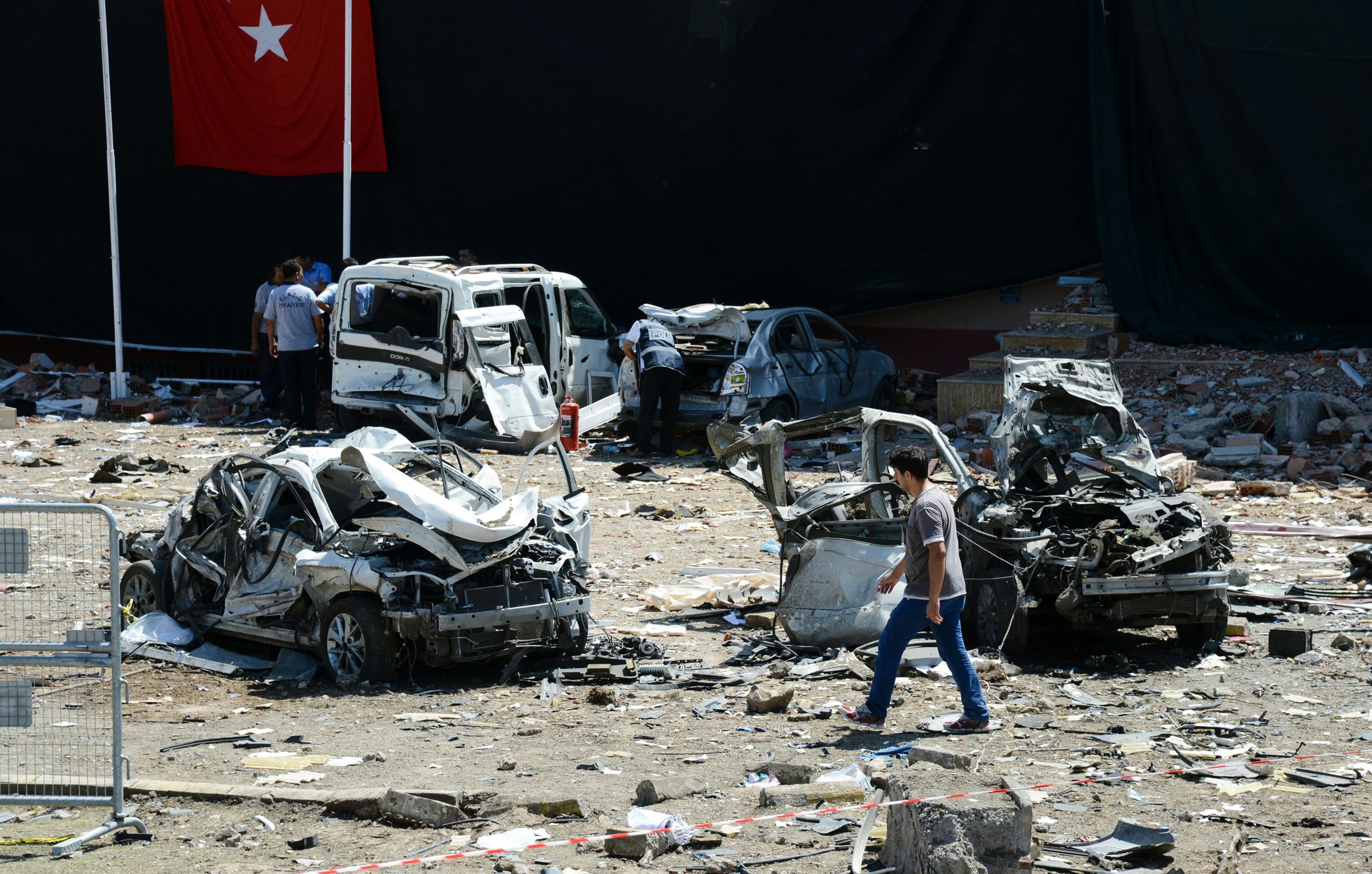 Turkish rescue workers stand by the wreckage of a vehicle as a Turkish police officer  inspects a destroyed car and a man walks among the remains at the blast scene following a car bomb attack on a police station in the eastern Turkish city of Elazig, on Aug. 18, 2016.