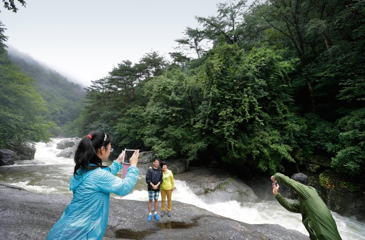 Chinese visitors take photographs at rapids at Mount Myonhyang, a North Korean tourist attraction