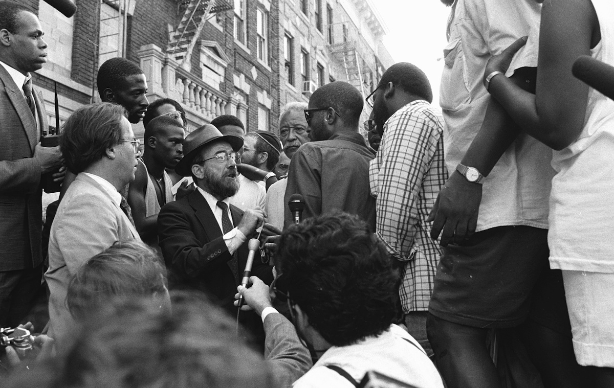 Mayor David Dinkins looks on while a Hasidic Jew and a black man argue during riots in Crown Heights in 1991.