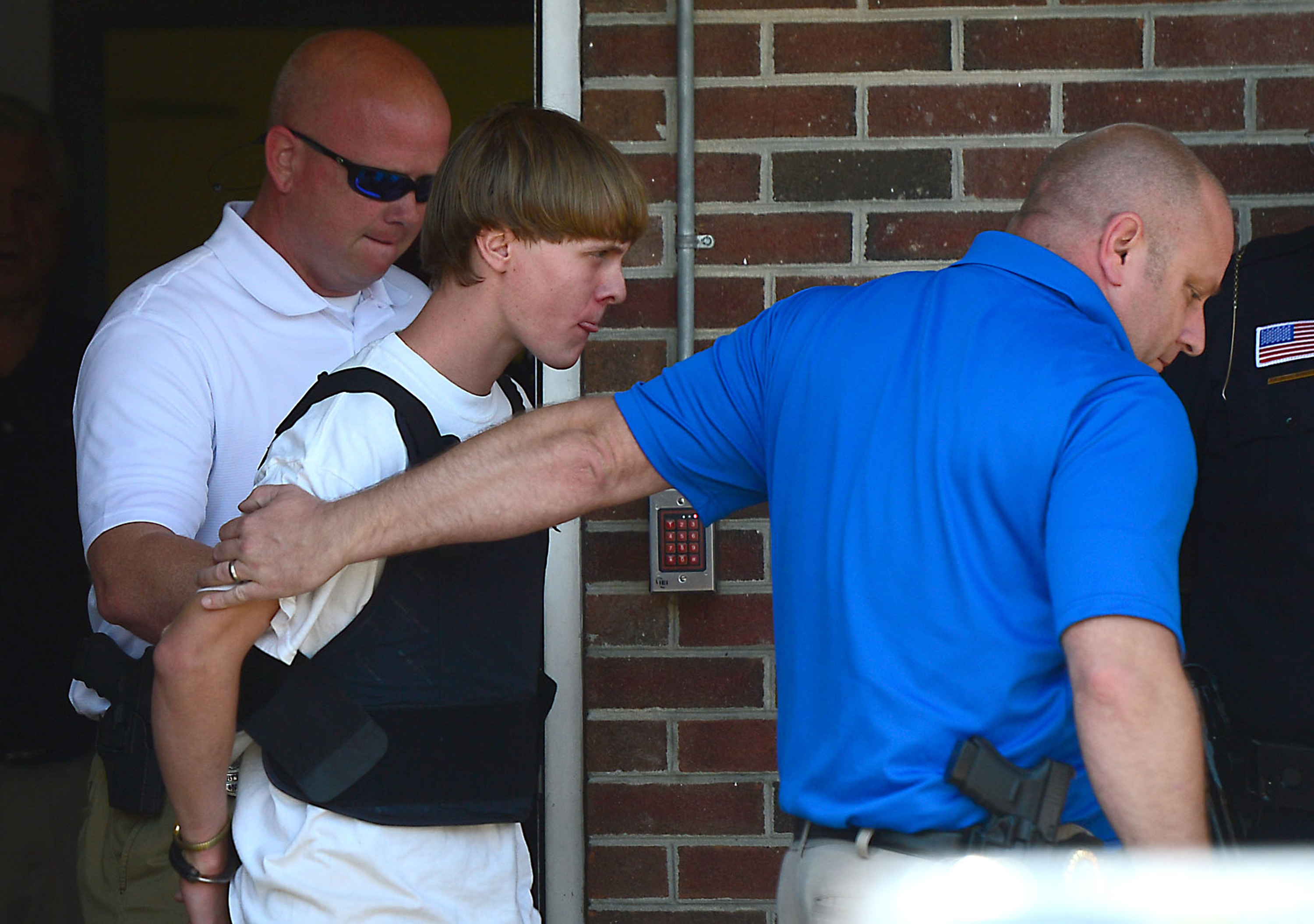 Charleston shooting suspect Dylann Roof is escorted from the Shelby Police Dept. Thursday, June 18, 2015 in Shelby, S.C.