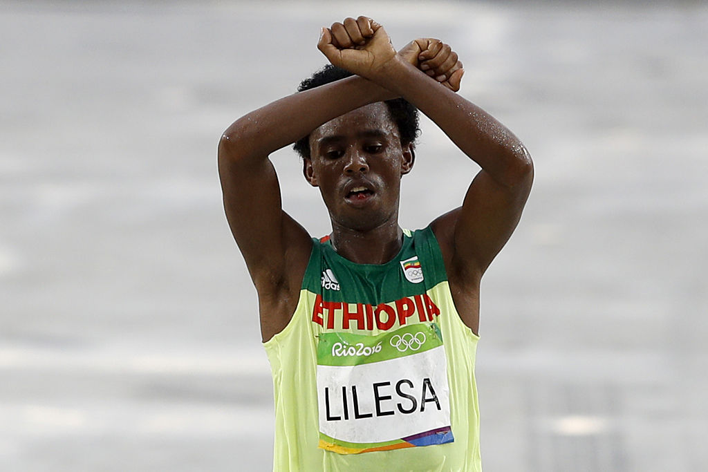 Ethiopia's Feyisa Lilesa (silver) crosses the finish line of the Men's Marathon athletics event during the Rio 2016 Olympic Games at the Sambodromo in Rio de Janeiro on August 21, 2016.                     Lilesa crossed his arms above his head as he finished the race as a protest against the Ethiopian government's crackdown on political dissent.