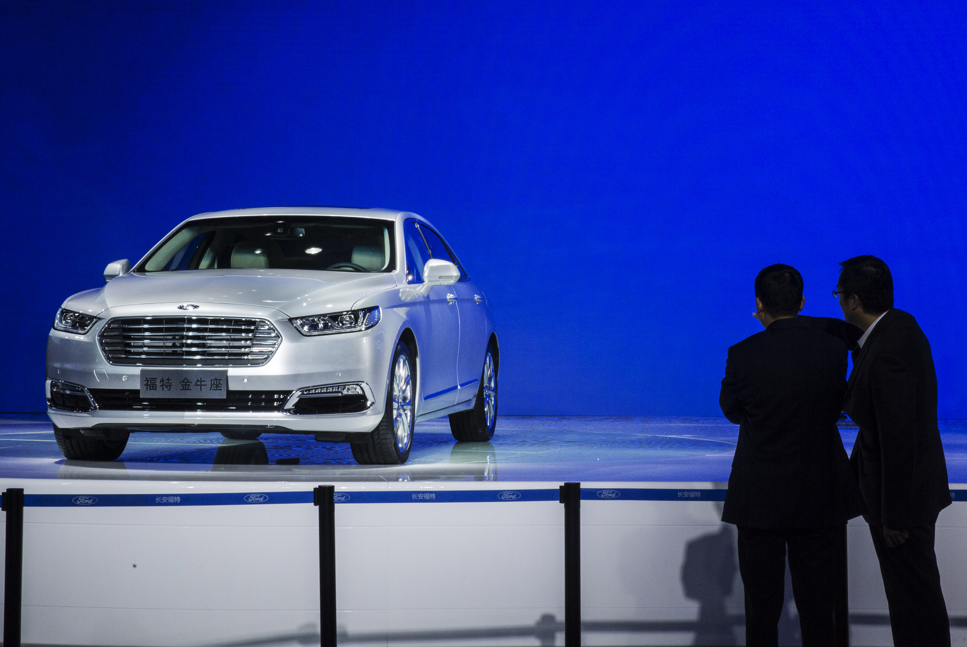Attendees look at at a Ford Motor Co. Taurus sedan on display during the China (Guangzhou) International Automobile Exhibition in Guangzhou, China, on Friday, Nov. 20, 2015.