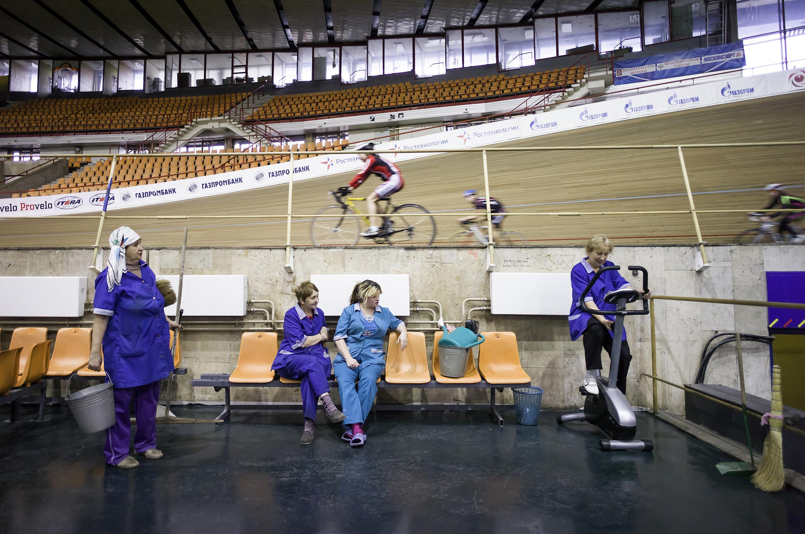 Cleaning women take a break at the Krylatskoye Sports Complex Velodrome in Moscow.