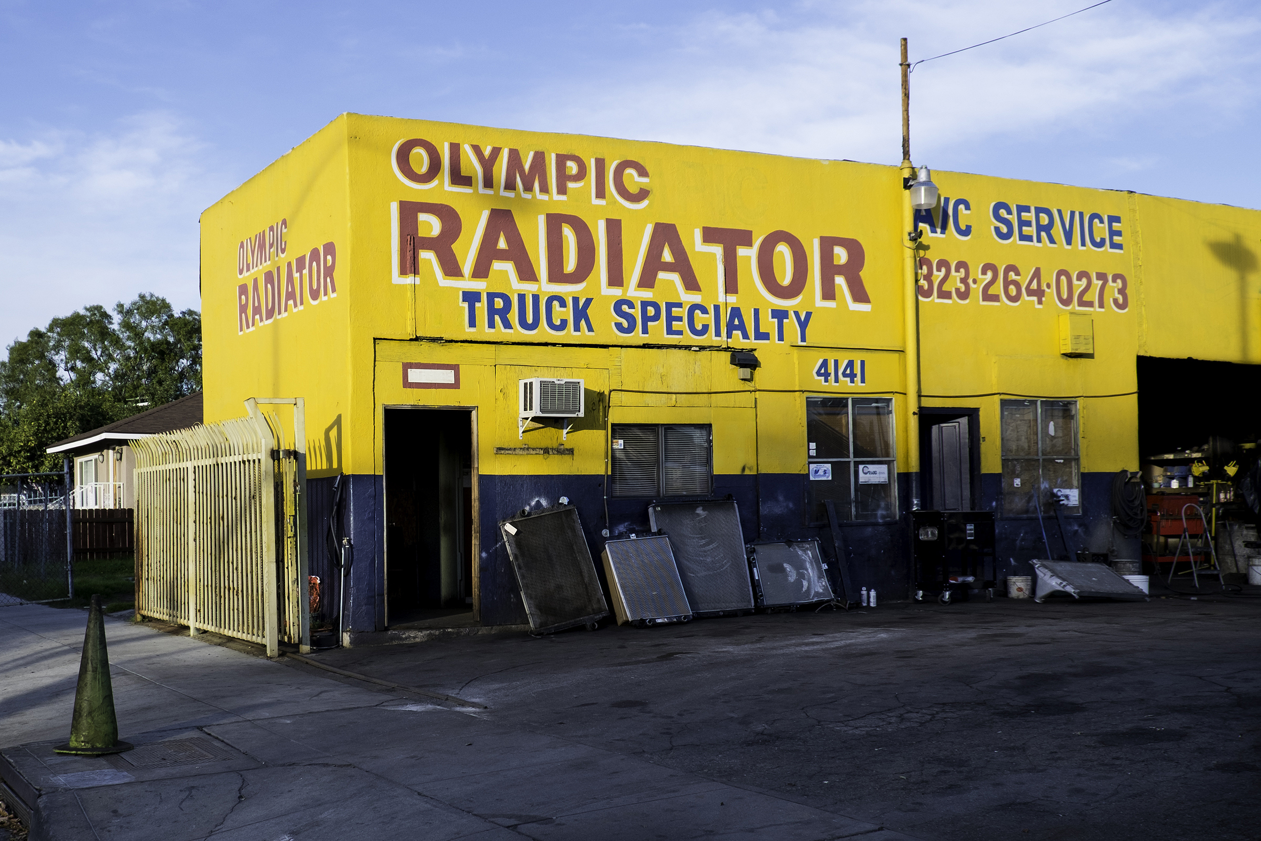 Olympic Radiator is located on Olympic Boulevard in Los Angeles, host of the 1932 and 1984 Summer Olympics, photographed in June 2012. The city changed the name of 10th Avenue to Olympic Boulevard; the street name and many similarly named businesses remain today.