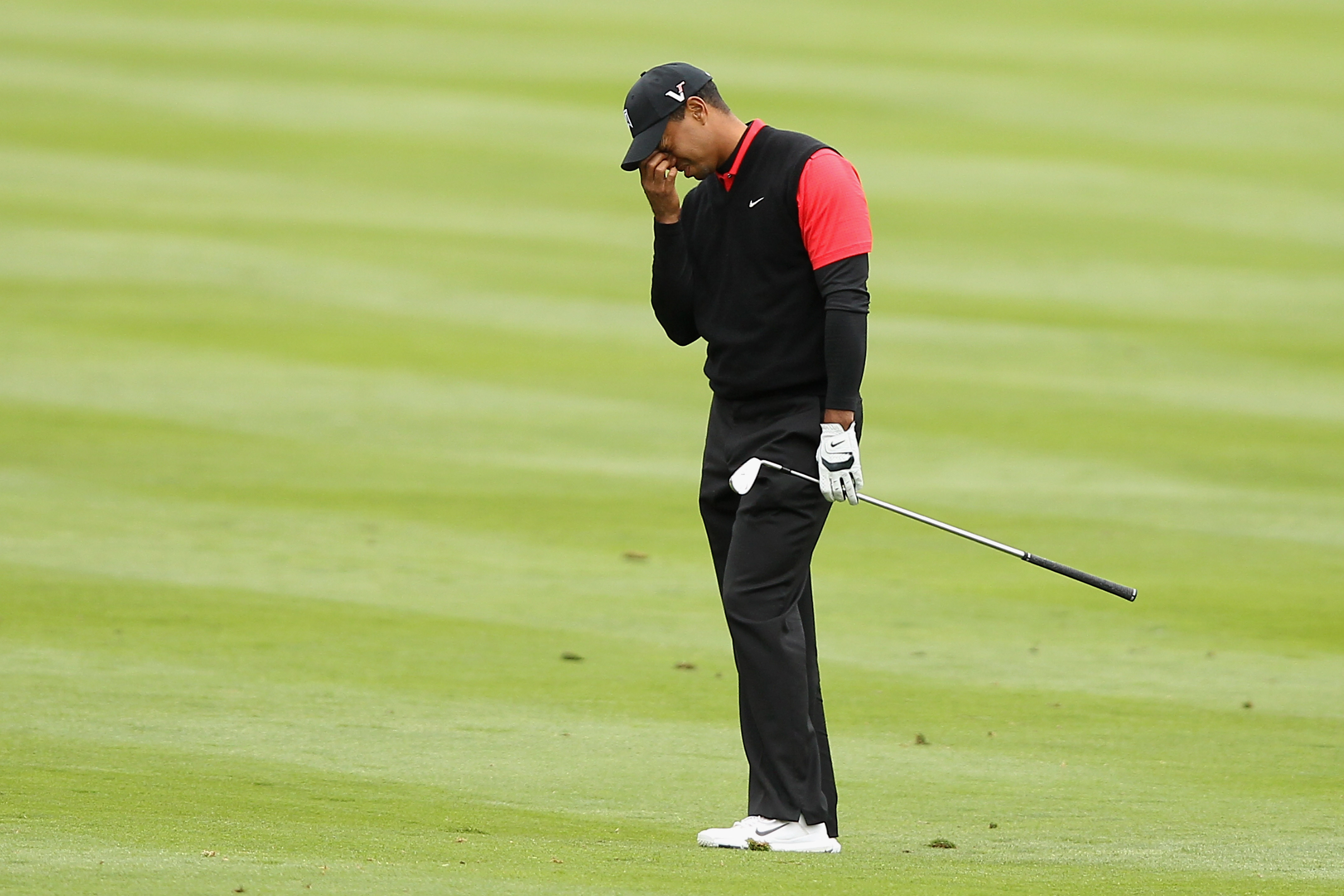 Tiger Woods reacts after hitting his second shot on the 14th hole during the final round of the AT&T Pebble Beach National Pro-Am at Pebble Beach Golf Links on February 12, 2012 in Pebble Beach, California.