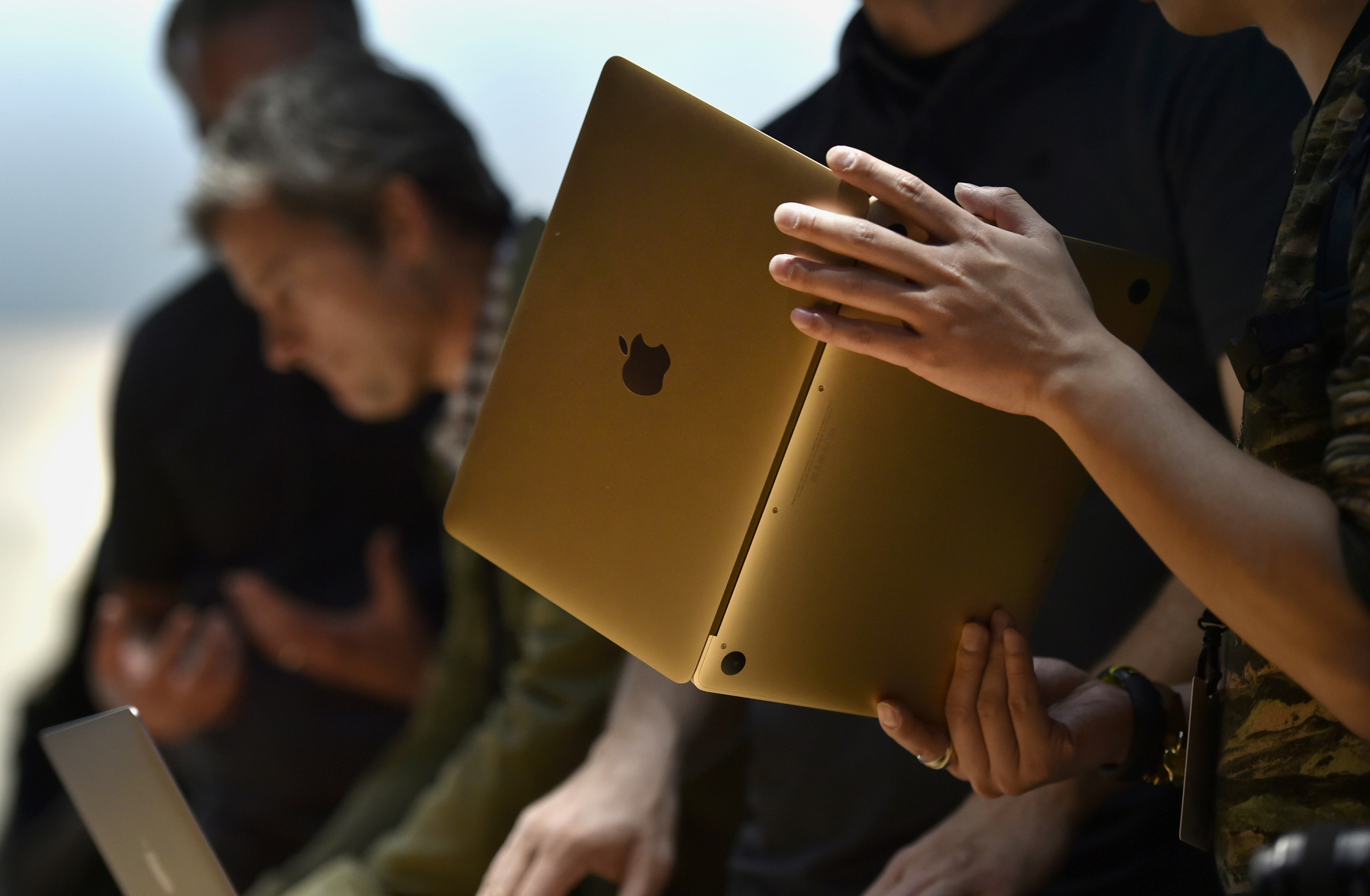Attendees view the Apple Inc. Macbook laptop during the company's Spring Forward event in San Francisco, California, U.S., on Monday, March 9, 2015.