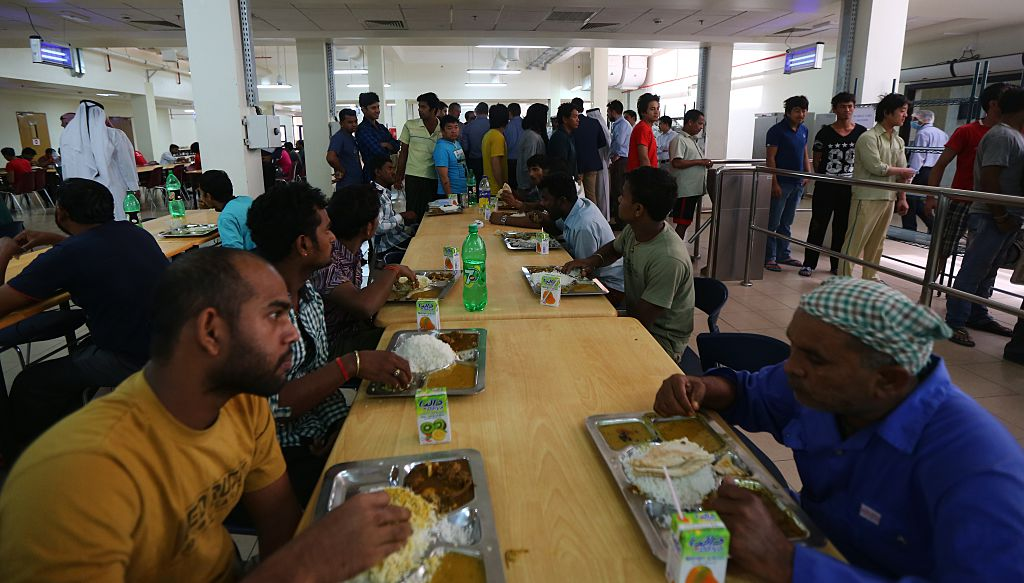 Foreign workers have lunch at the cafeteria of the new labour city in Doha, on May 3, 2015, which was built by the Qatari government and is currently housing some 16,000 workers. The Qatari government has announced new projects to provide better accommodation for up to one million migrant workers. Today they organised a media tour of existing housing camps and new ones.  AFP PHOTO / MARWAN NAAMANI        (Photo credit should read MARWAN NAAMANI/AFP/Getty Images)